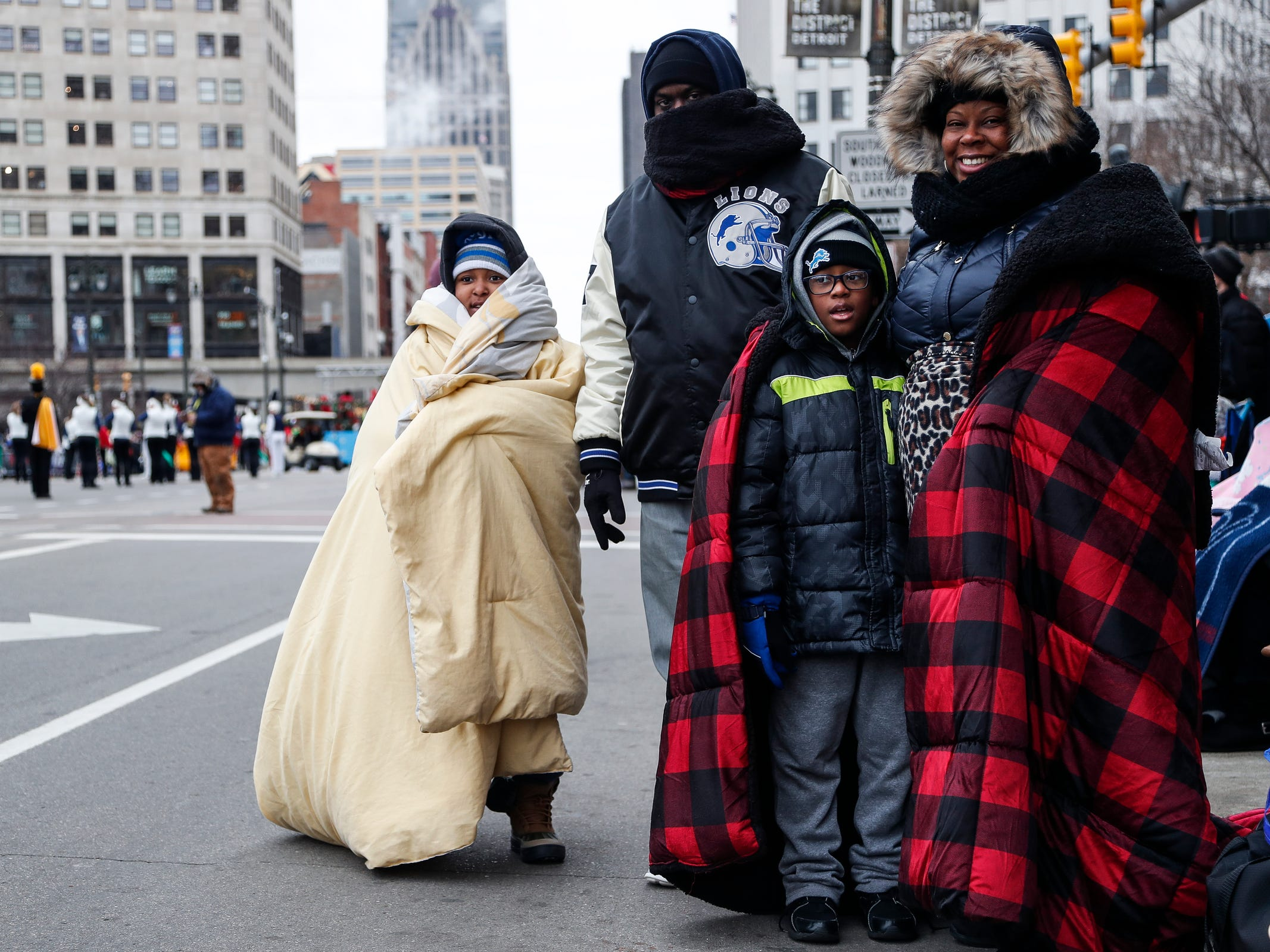 From left, Deraj Tigner, 7, Victor Griffin, Kevin Dean, 7, and his mother Arthelrus Day, try to stay warm on Woodward Avenue during the 92nd America's Thanksgiving Day Parade in Detroit, Thursday, Nov. 22, 2018.