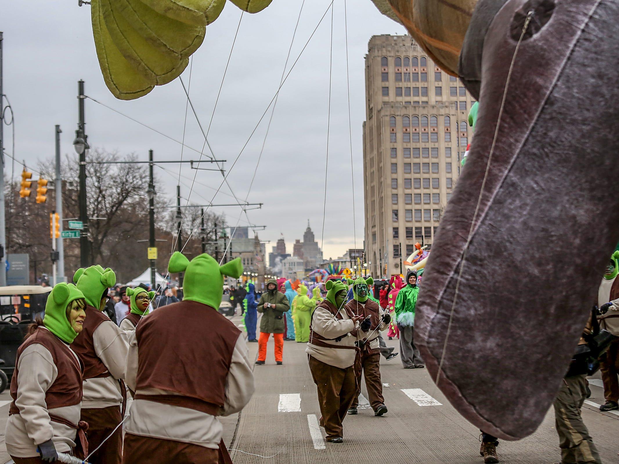 Shrek float handlers take a moment, during America's Thanksgiving Parade in Detroit on Thursday, Nov. 22, 2018.