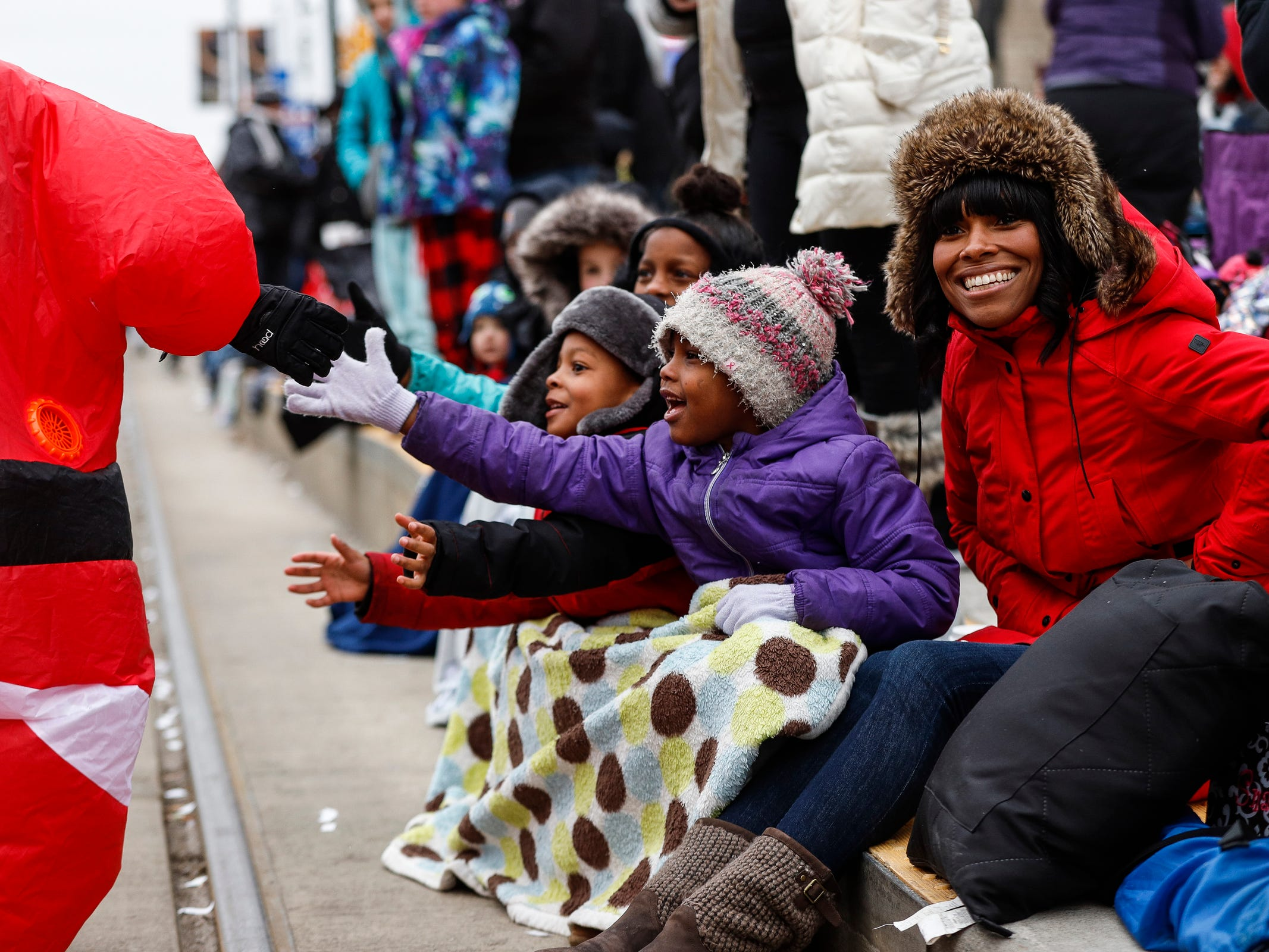 From center left, Taliyah Jones, 11, Jeremiah Jones, 5,  Quamiya Walker, 6, all of Detroit and their aunt Nichole Jones of Fraster, cheer for Turkey Trot runners on  Woodward Avenue in Detroit, Thursday, Nov. 22, 2018.