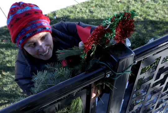 Linda Majka of South Lyon and the mother of Jeff Heinanen, adds Christmas decorations to the fence of Heinanen Engineering on Wednesday, Nov. 21, 2018 where a 53 foot Blue Spruce has been installed as South Lyon's official tree.