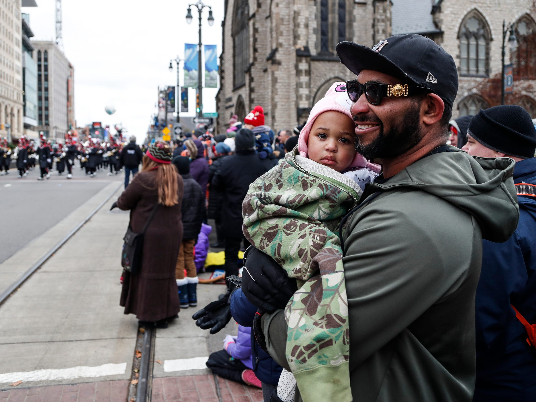 Mark Ephraim and his daughter Marie, 2, watch the parade on Woodward Avenue during the 92nd America's Thanksgiving Day Parade in Detroit, Thursday, Nov. 22, 2018.