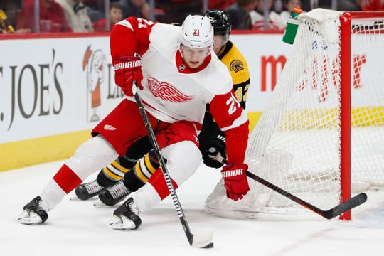 Detroit Red Wings defenseman Dennis Cholowski (21) skates away from Boston Bruins right wing David Backes (42) during the first period at Little Caesars Arena on Wednesday, Nov. 21, 2018.