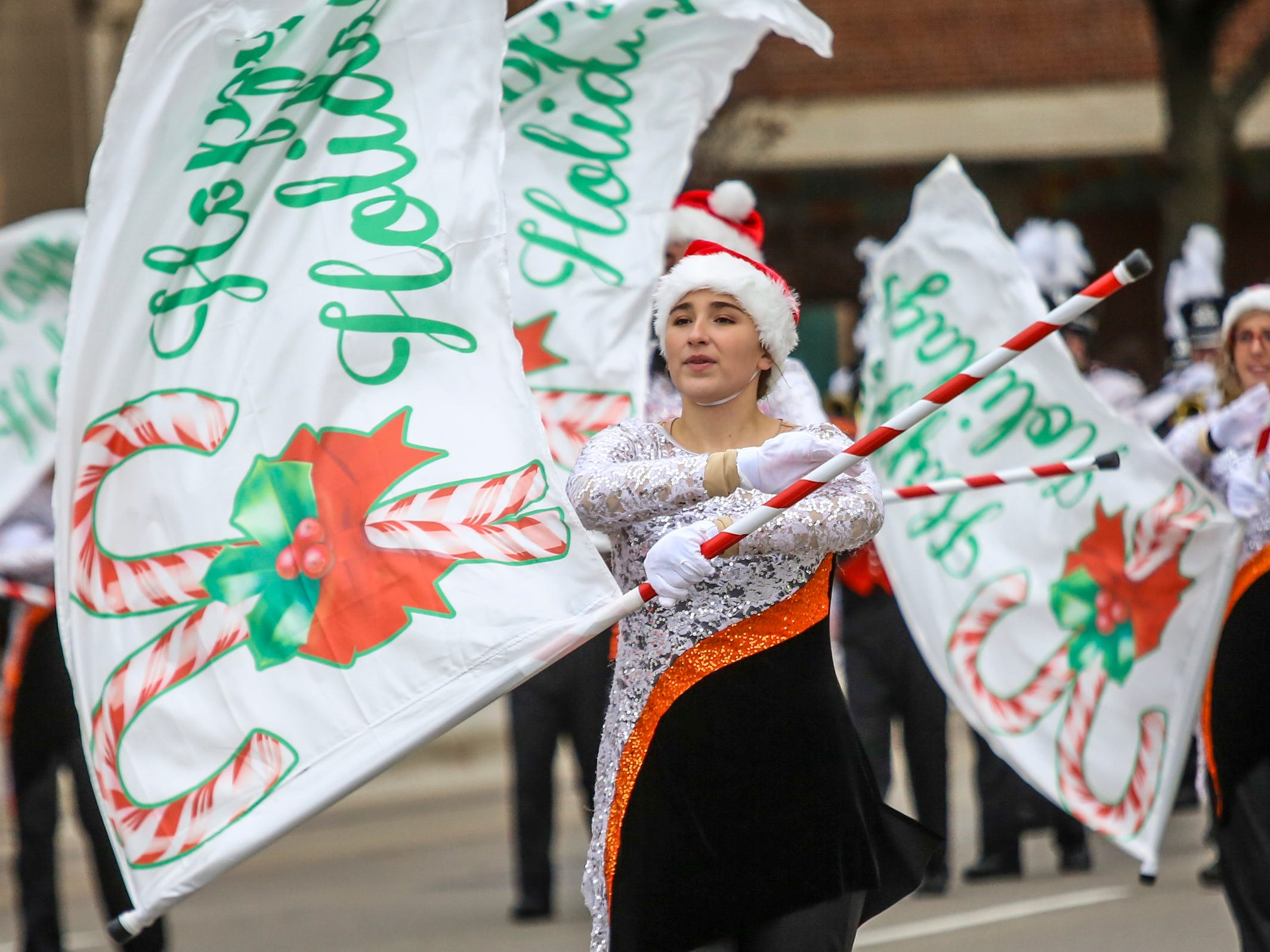 Brighton High School marching band flag guard performs, during America's Thanksgiving Parade in Detroit on Thursday, Nov. 22, 2018.