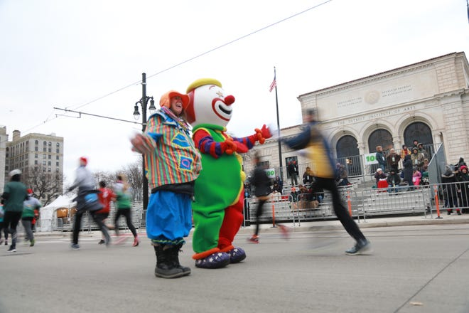 Clowny and Lin Szylkowski-Fish, 52, of Royal oak high five runners participating in the Turkey Trot on Thursday, Nov. 22, 2018 in Detroit.