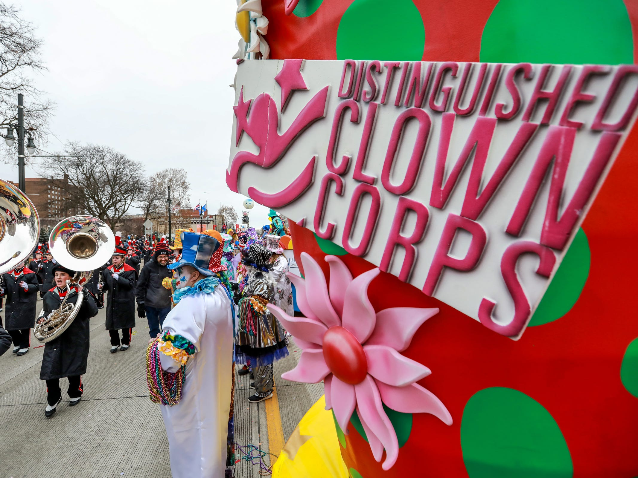 The Distinguished Clown Corps watch the parade go by and they wait until their time comes to join in, during America's Thanksgiving Parade in Detroit on Thursday, Nov. 22, 2018.