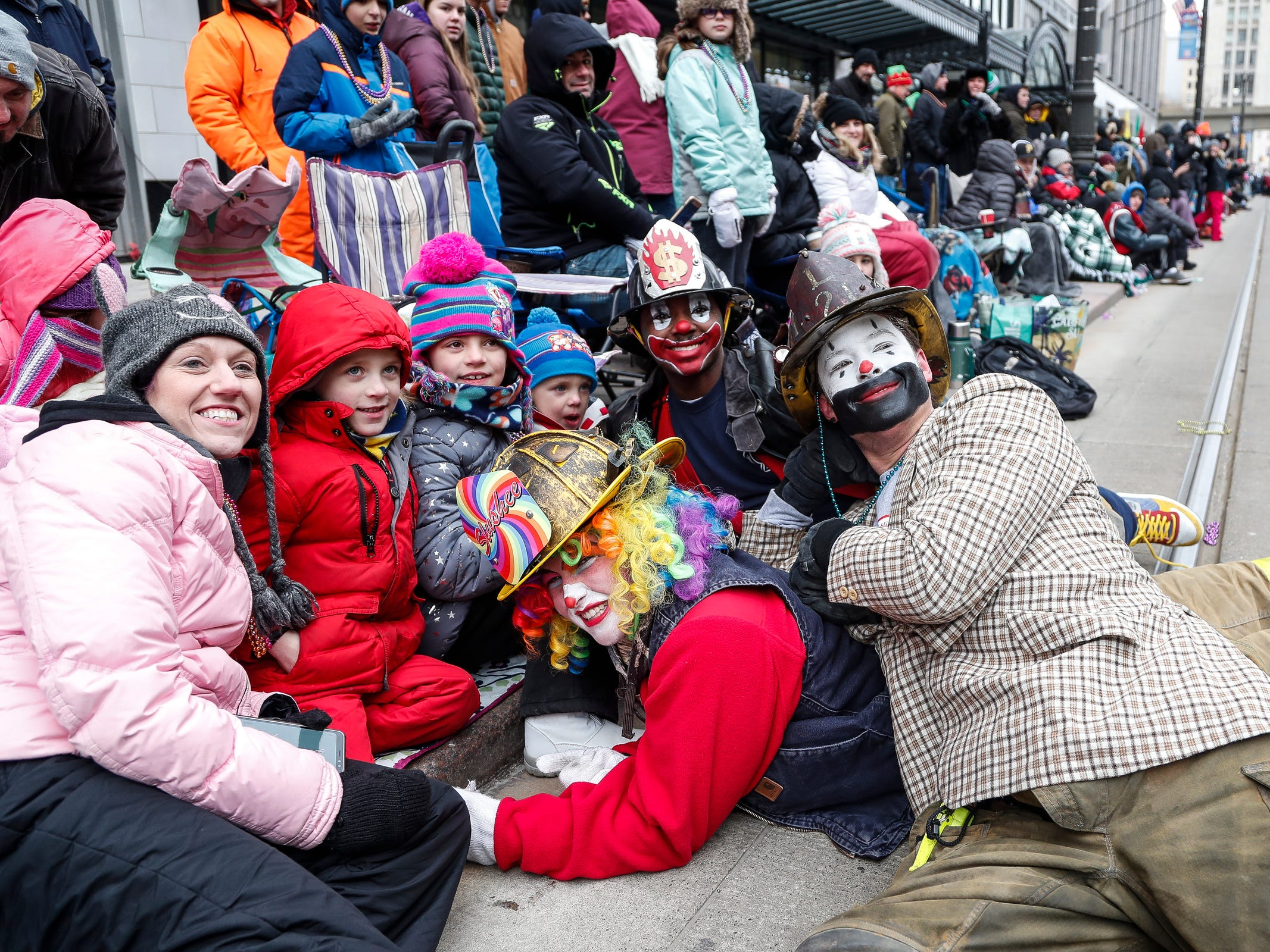 Detroit Fire Department clowns pose for a photo with spectators during the 92nd America's Thanksgiving Day Parade in Detroit, Thursday, Nov. 22, 2018.