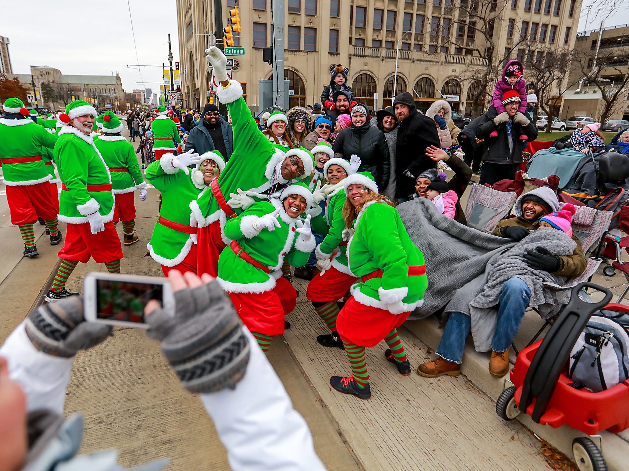 Santa's elves take a photo with the crowd during America's Thanksgiving Parade in Detroit on Thursday, Nov. 22, 2018.