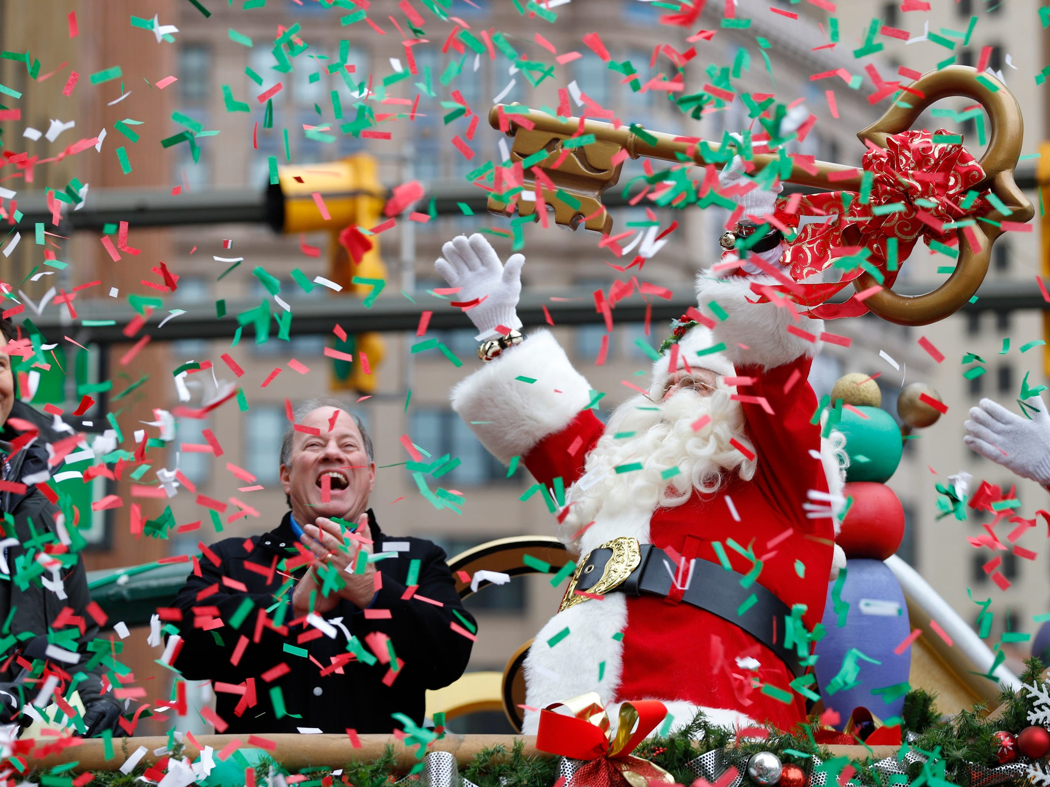 Santa Claus gets the key to the city from mayor Mike Duggan during the 92nd America's Thanksgiving Day Parade in Detroit, Thursday, Nov. 22, 2018.