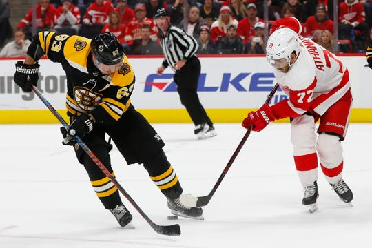 Detroit Red Wings center Andreas Athanasiou (72) steals the puck from Boston Bruins left wing Brad Marchand (63) in overtime during an NHL hockey game Wednesday, Nov. 21, 2018, in Detroit. Detroit won 3-2.