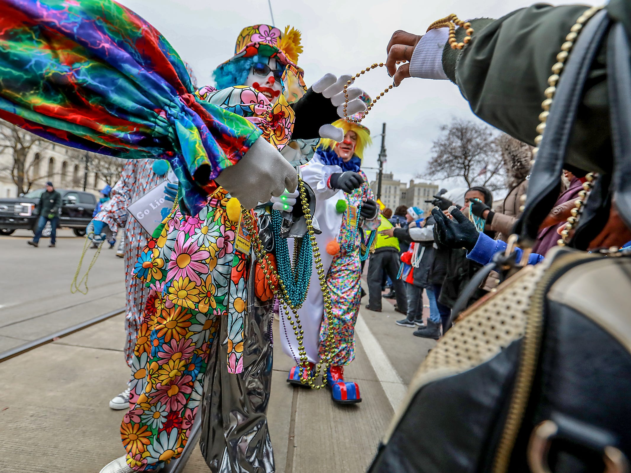 Distinguished Clown Corps members hand out beads to the crowd, during America's Thanksgiving Parade in Detroit on Thursday, Nov. 22, 2018.