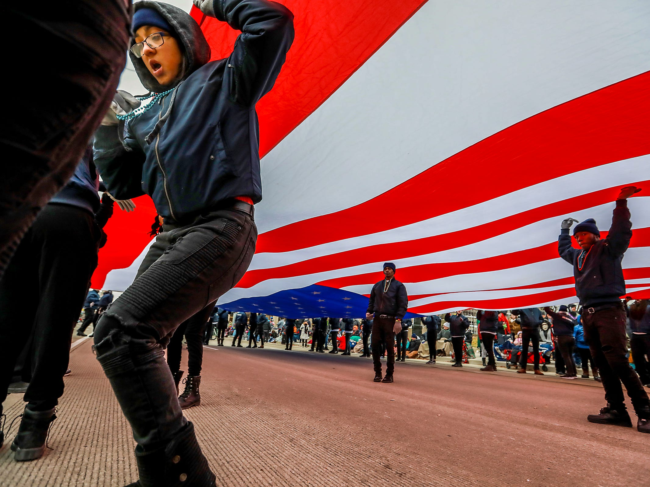 Parade marchers with Shinola Hotel carry an American flag down Woodward avenue, during America's Thanksgiving Parade in Detroit on Thursday, Nov. 22, 2018.