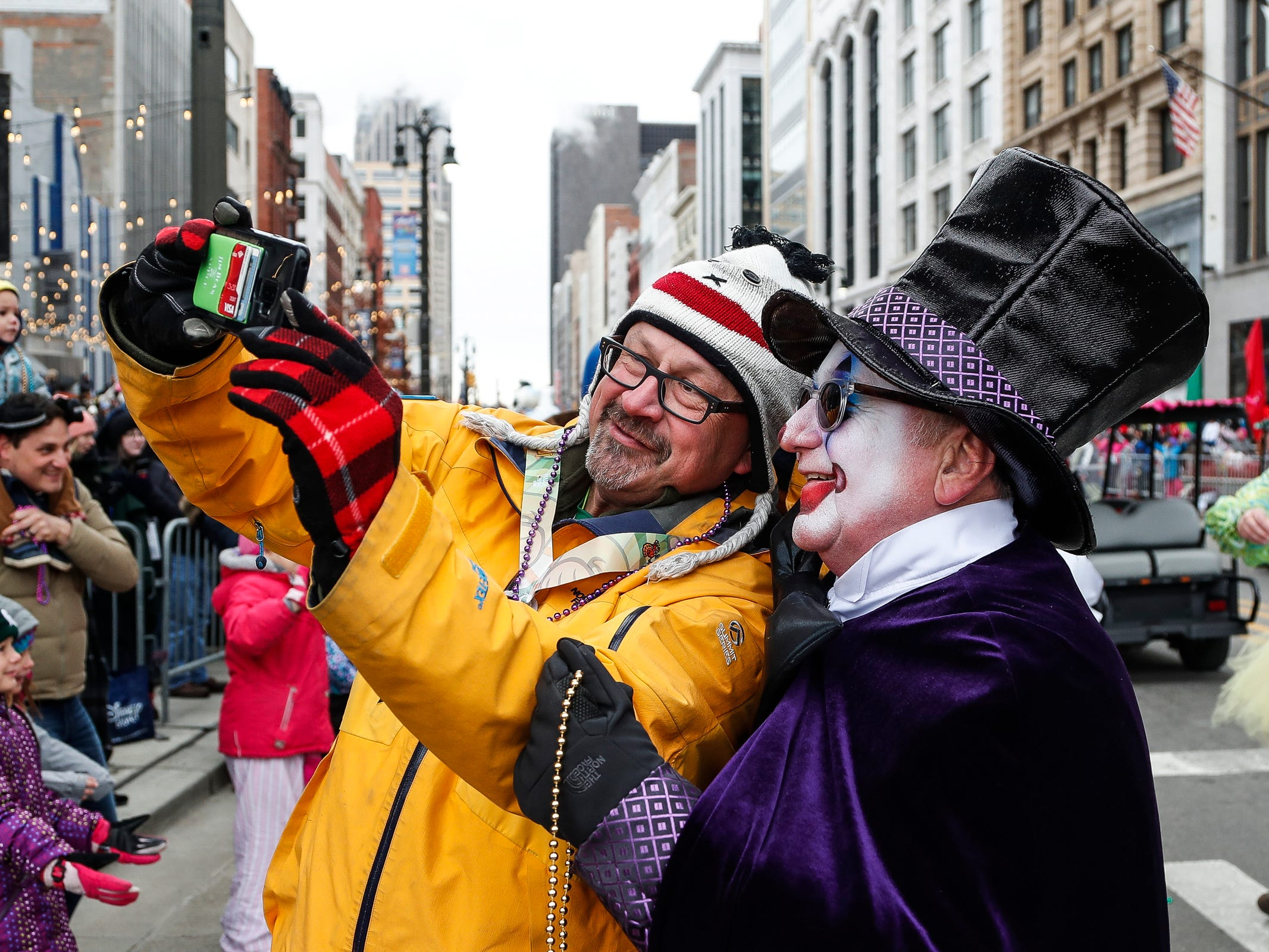 David Haener of New Boston takes a selfie with a clown during the 92nd America's Thanksgiving Day Parade in Detroit, Thursday, Nov. 22, 2018.
