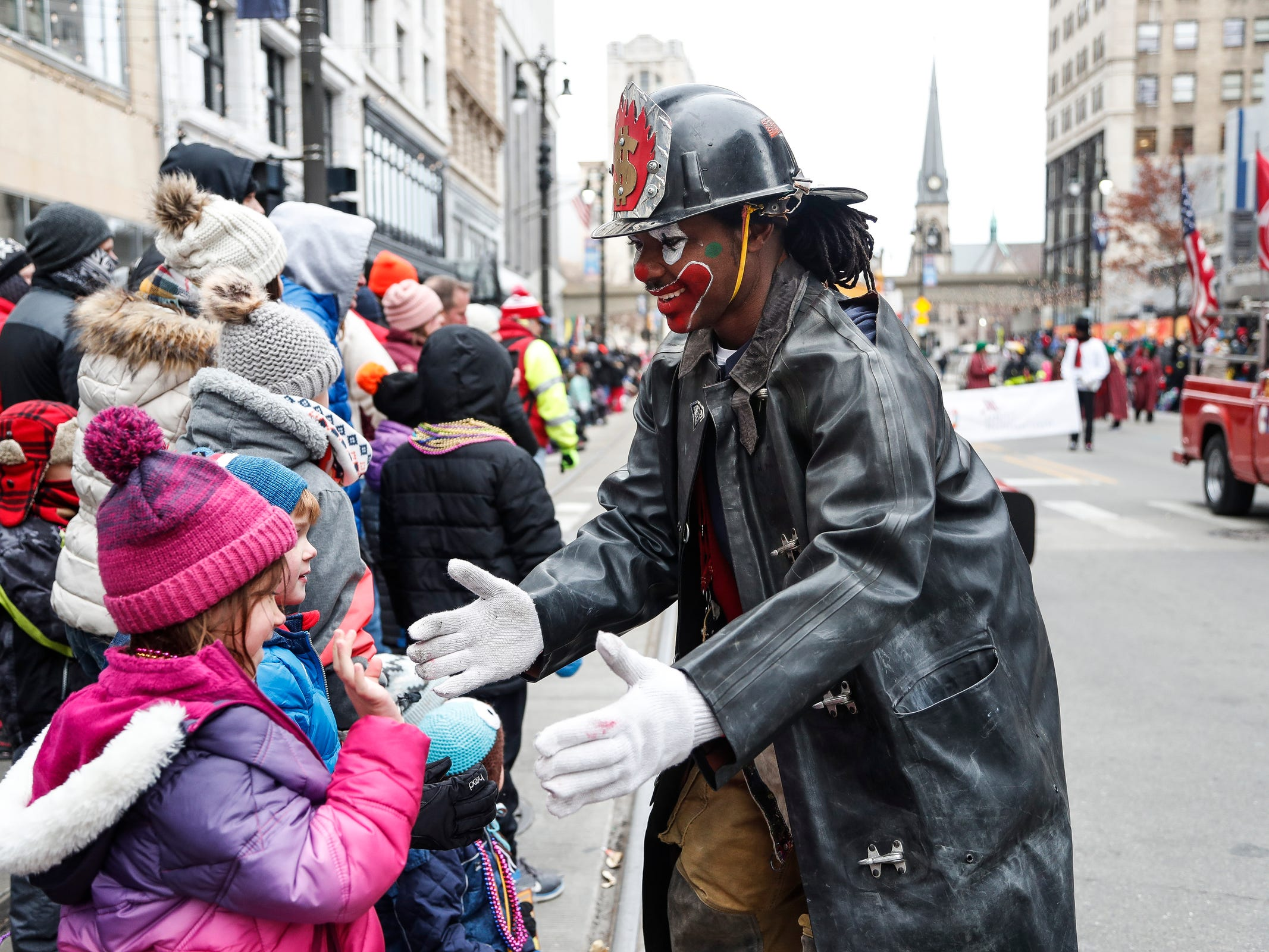 Detroit Fire Department clown Melvin Bills high fives Kate Stucky, 6, and her brother Henry, 4, both of Troy during the 92nd America's Thanksgiving Day Parade in Detroit, Thursday, Nov. 22, 2018.