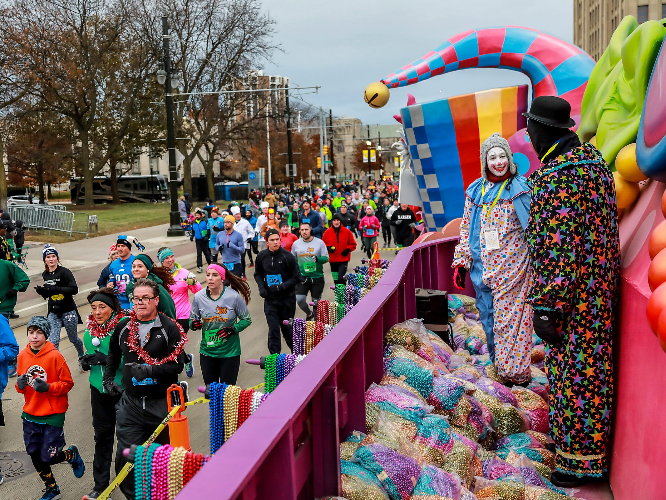 Runners participate in the Turkey Trot before the start of America's Thanksgiving Parade while clowns, Rosie Feinbloom, 17, of Bloomfield Hills and her father look on, in Detroit on Thursday, Nov. 22, 2018.