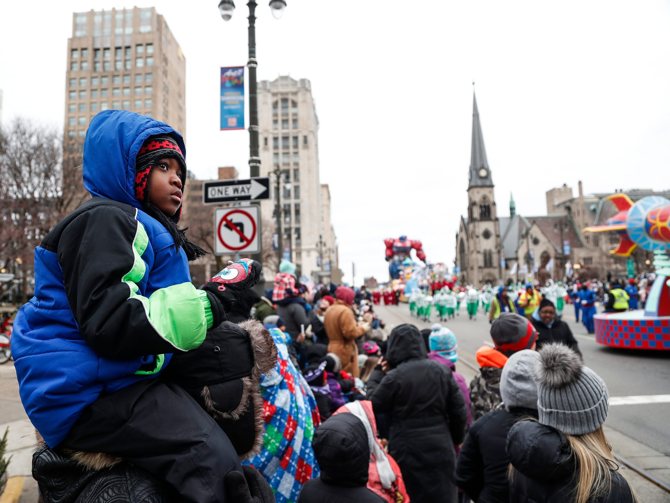 Lee Patterson III, 5, sits on his father's shoulder as they watch the 92nd America's Thanksgiving Day Parade on Woodward AvenueÊin Detroit, Thursday, Nov. 22, 2018.