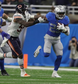 Lions running back Theo Riddick runs by Bears linebacker Danny Trevathan during the first half on Thursday, Nov. 22, 2018, at Ford Field.