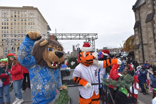 Lions mascot Rory and the Tigers mascot PAWS wave to the crowds along Woodward Ave.