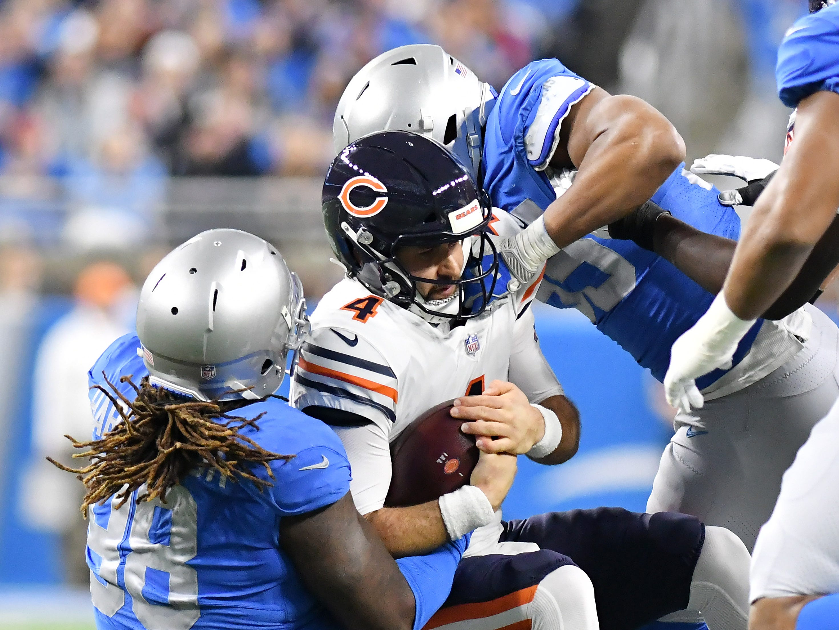 Lions' Damon Harrison Sr. (98) and Romeo Okwara, top, sack Chicago quarterback Chase Daniel (4) In the first quarter.