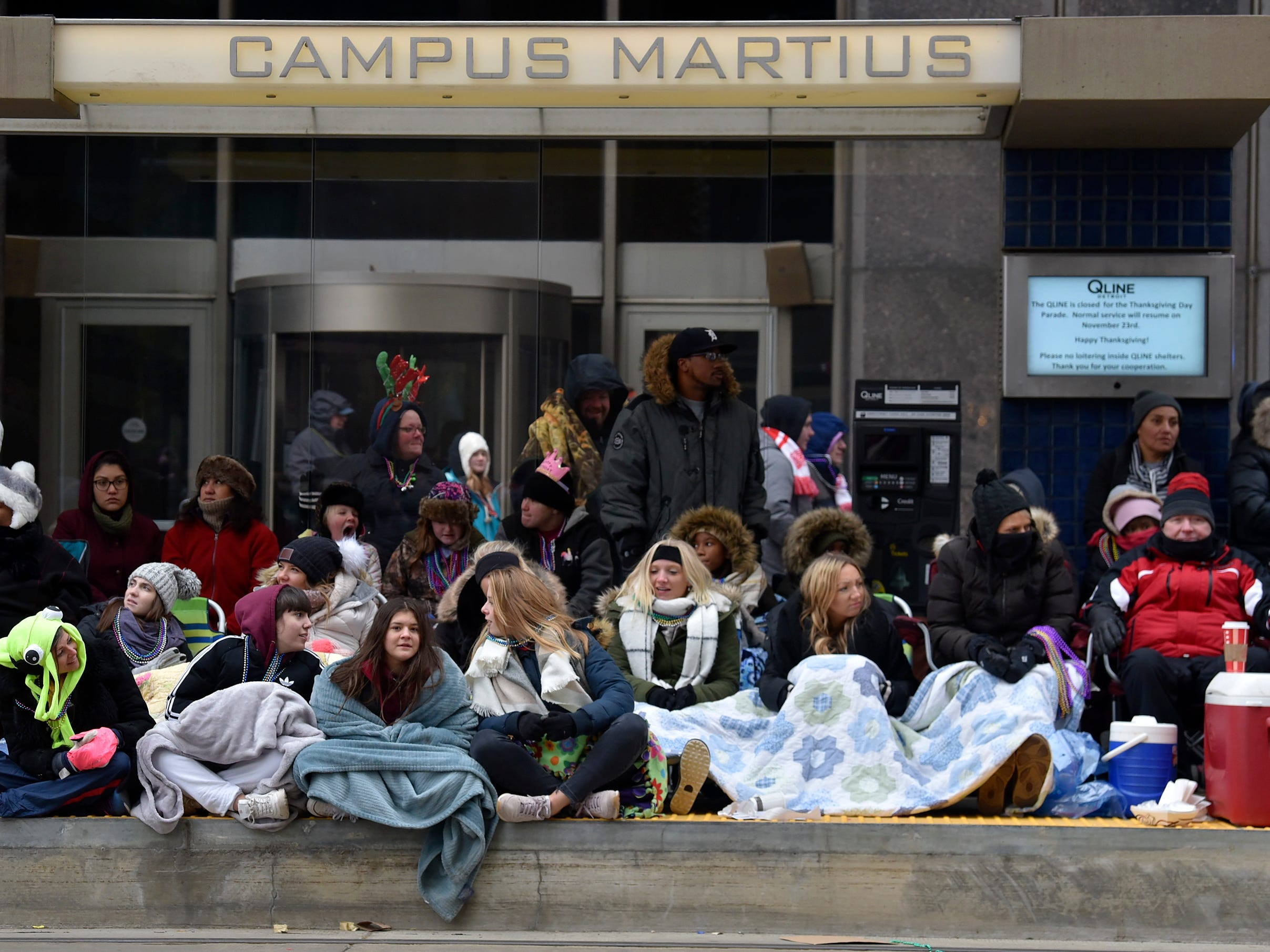 People keep warm under blankets at the Campus Martius Q Line stop.