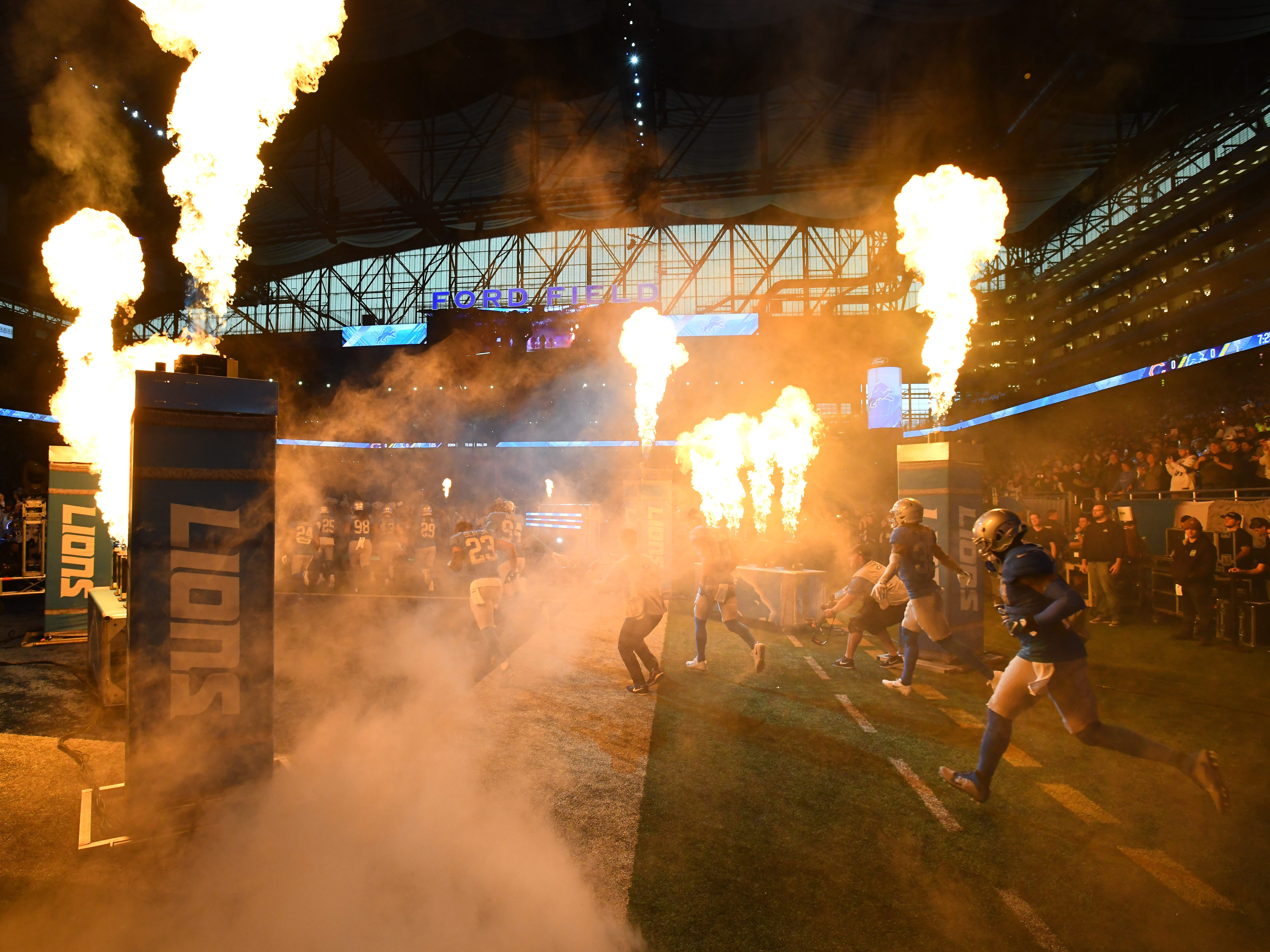 The Detroit Lions charge out of the tunnel before taking on the Chicago Bears at Ford Field on Thanksgiving Day.