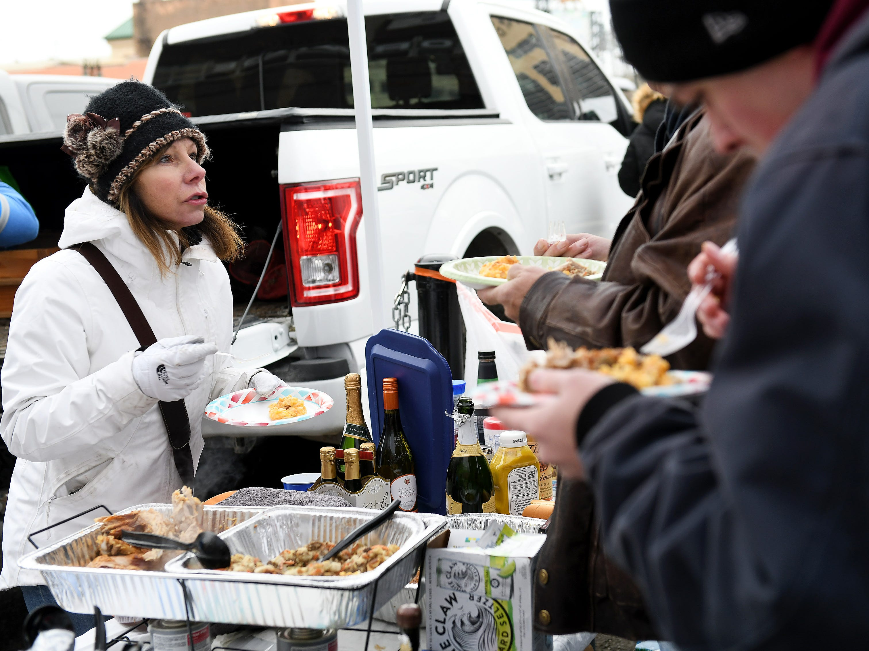 Linda Bonell of Plymouth eats some of the turkey dinner she made for everyone during tailgating before the game.  Detroit Lions vs Chicago Bears on Thanksgiving Day at Ford Field in Detroit on Nov. 22, 2018.