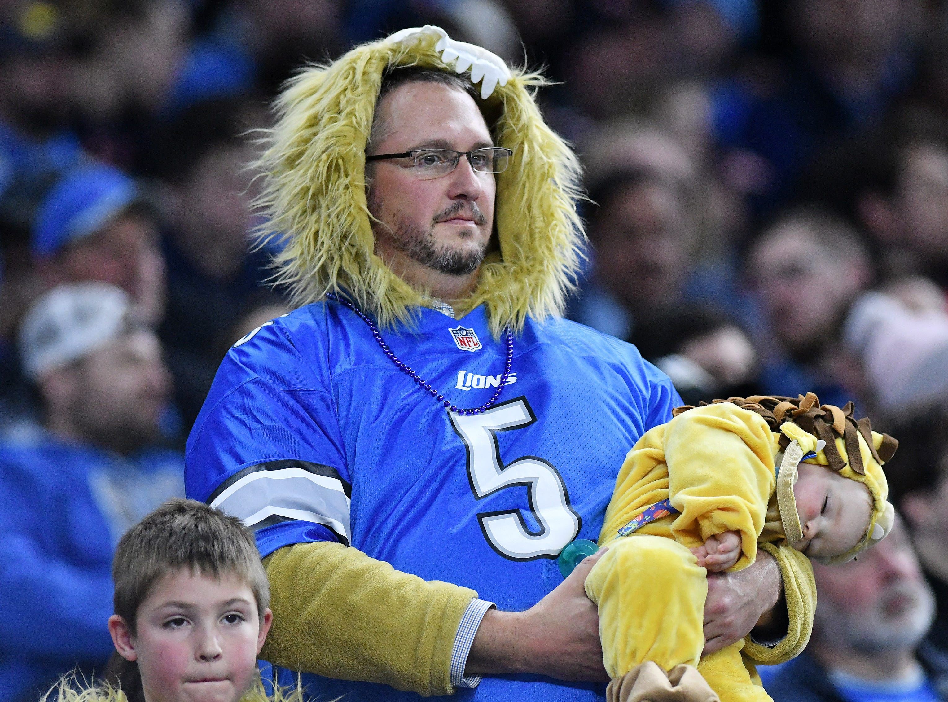Papa Lions holds one of his sleeping cubs In the second quarter. Detroit Lions vs Chicago Bears on Thanksgiving Day at Ford Field in Detroit on Nov. 22, 2018. (Robin Buckson / Detroit News)
