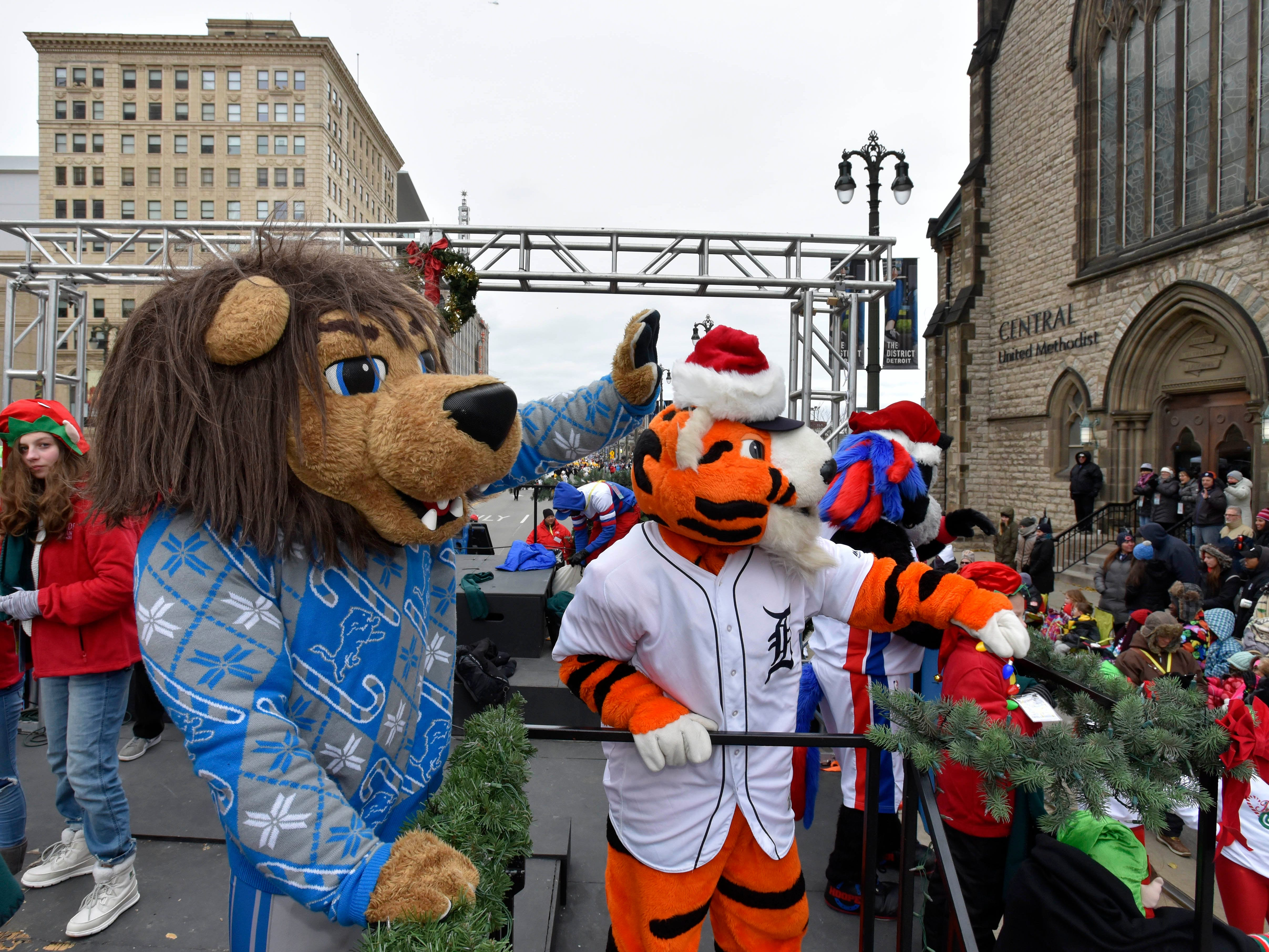 Lions mascot Rory, left, Tigers mascot PAWS and Pistons mascot Hooper ride the 104.3 WOMC float.