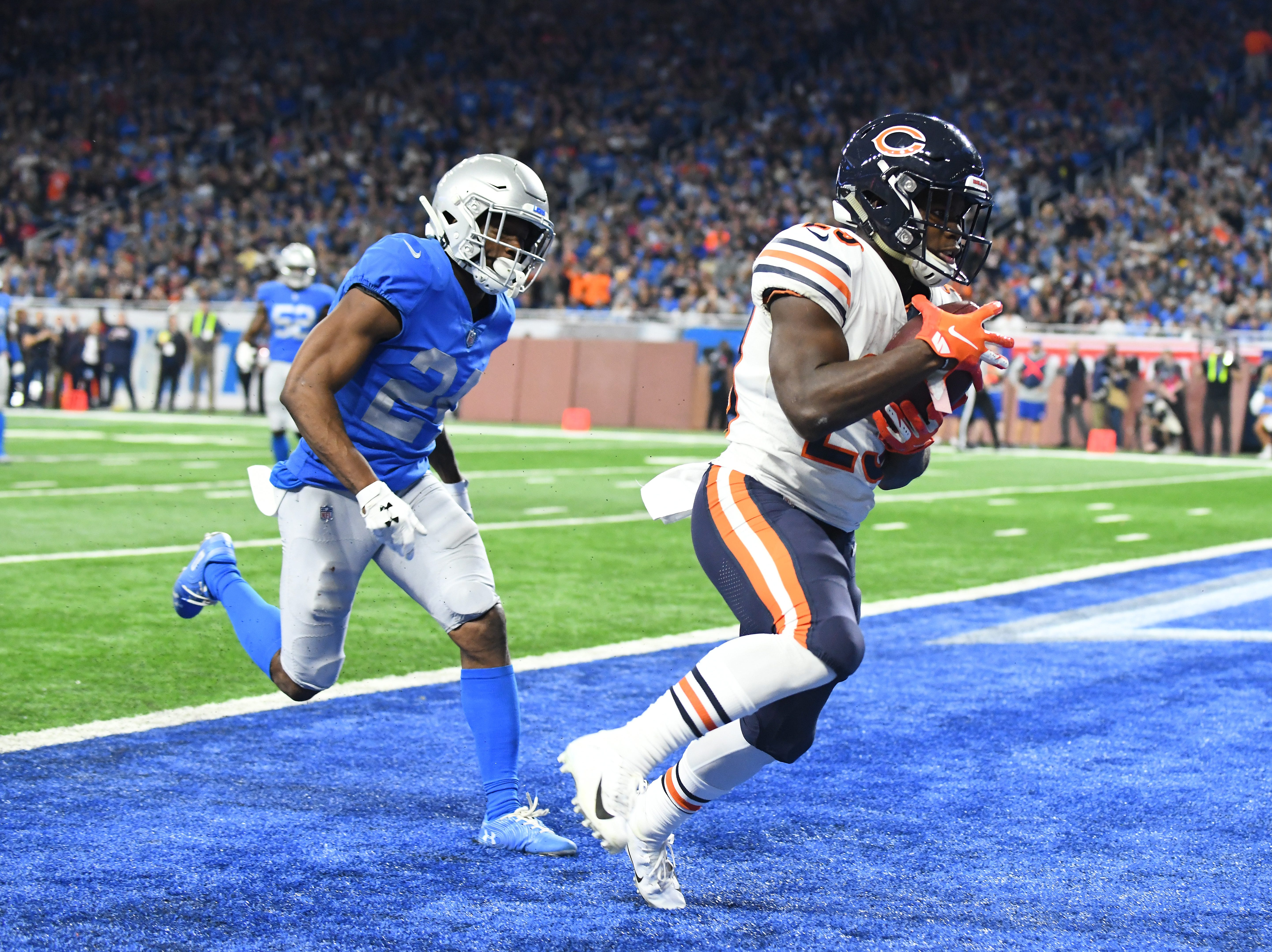 Bears' Tarik Cohen goes into the end zone after a reception with Lions' Nevin Lawson defending in the fourth quarter.