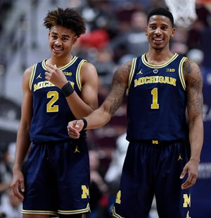 Michigan's Jordan Poole and Charles Matthews smile during the final minutes of the win over Providence.