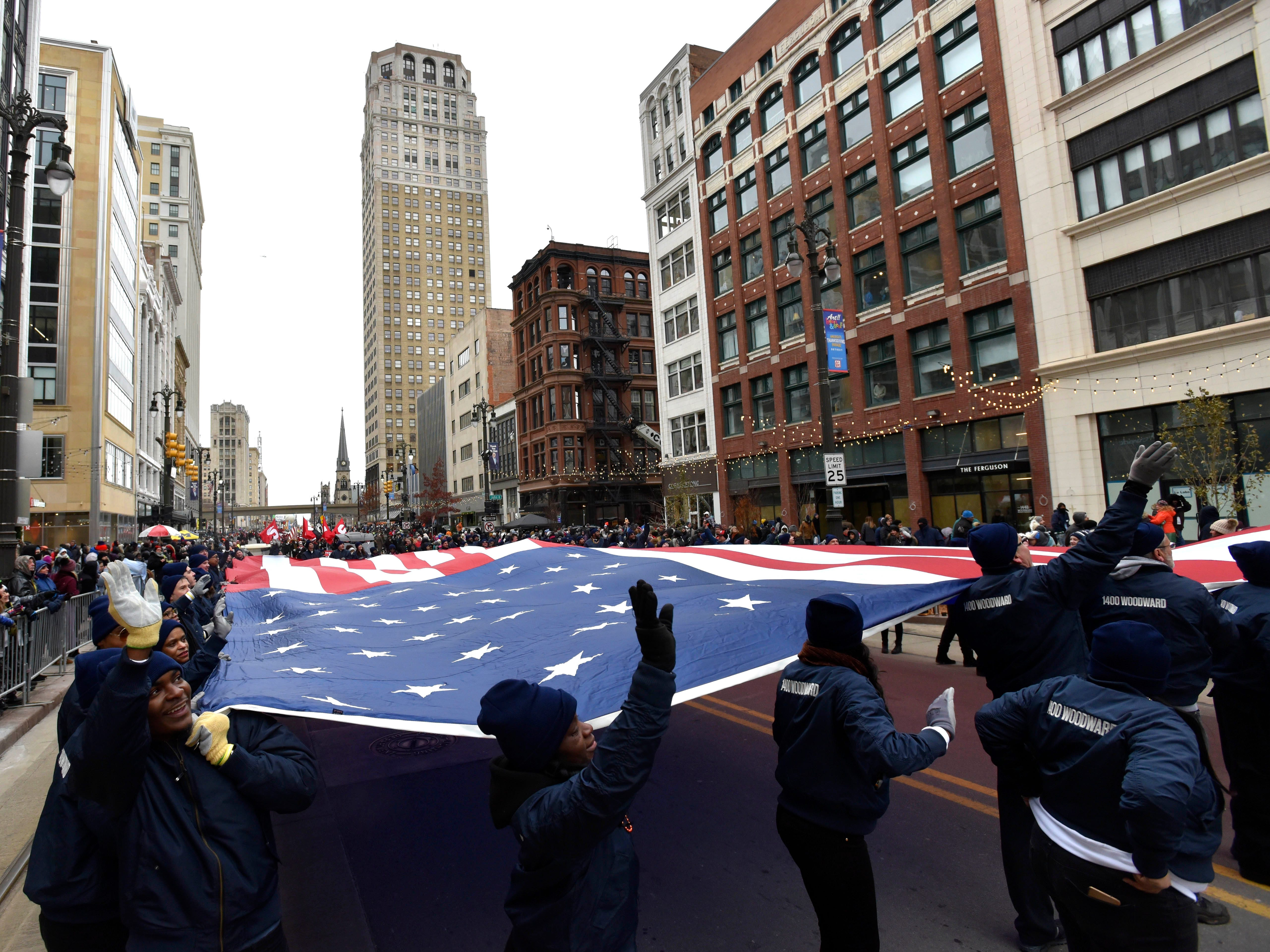 People wave with the U.S. flag from Shinola Detroit.
