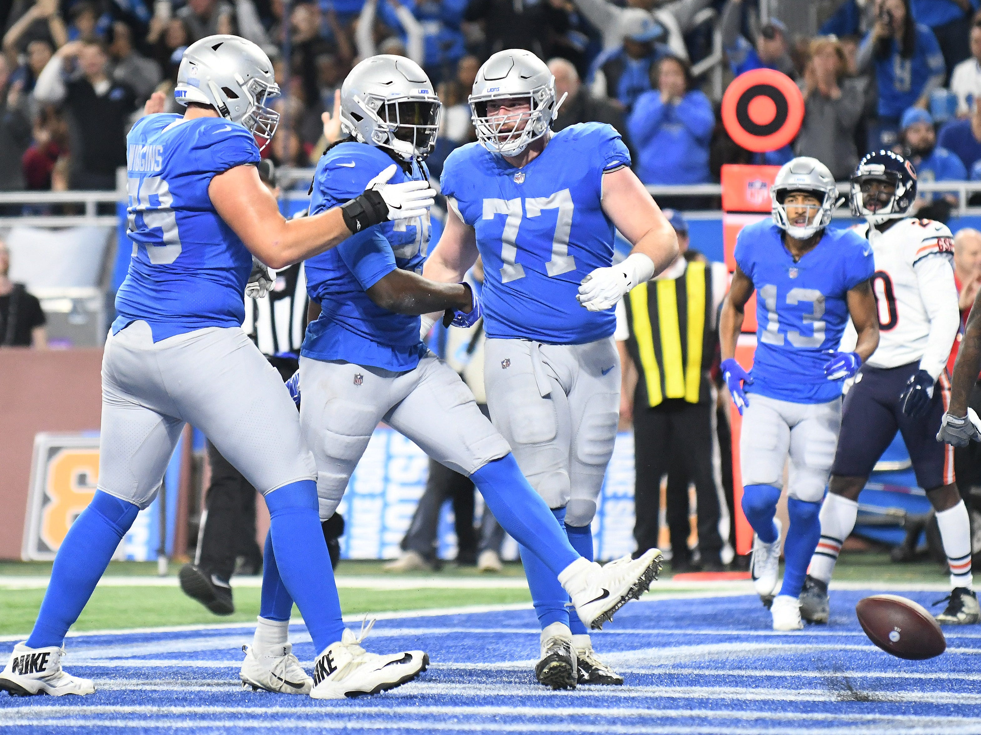 Lions' LaGarrette Blount, center, celebrates his second half touchdown with Kenny Wiggins, left, and Frank Ragnow (77) In the second quarter. Detroit Lions vs Chicago Bears on Thanksgiving Day at Ford Field in Detroit on Nov. 22, 2018. (Robin Buckson / Detroit News)