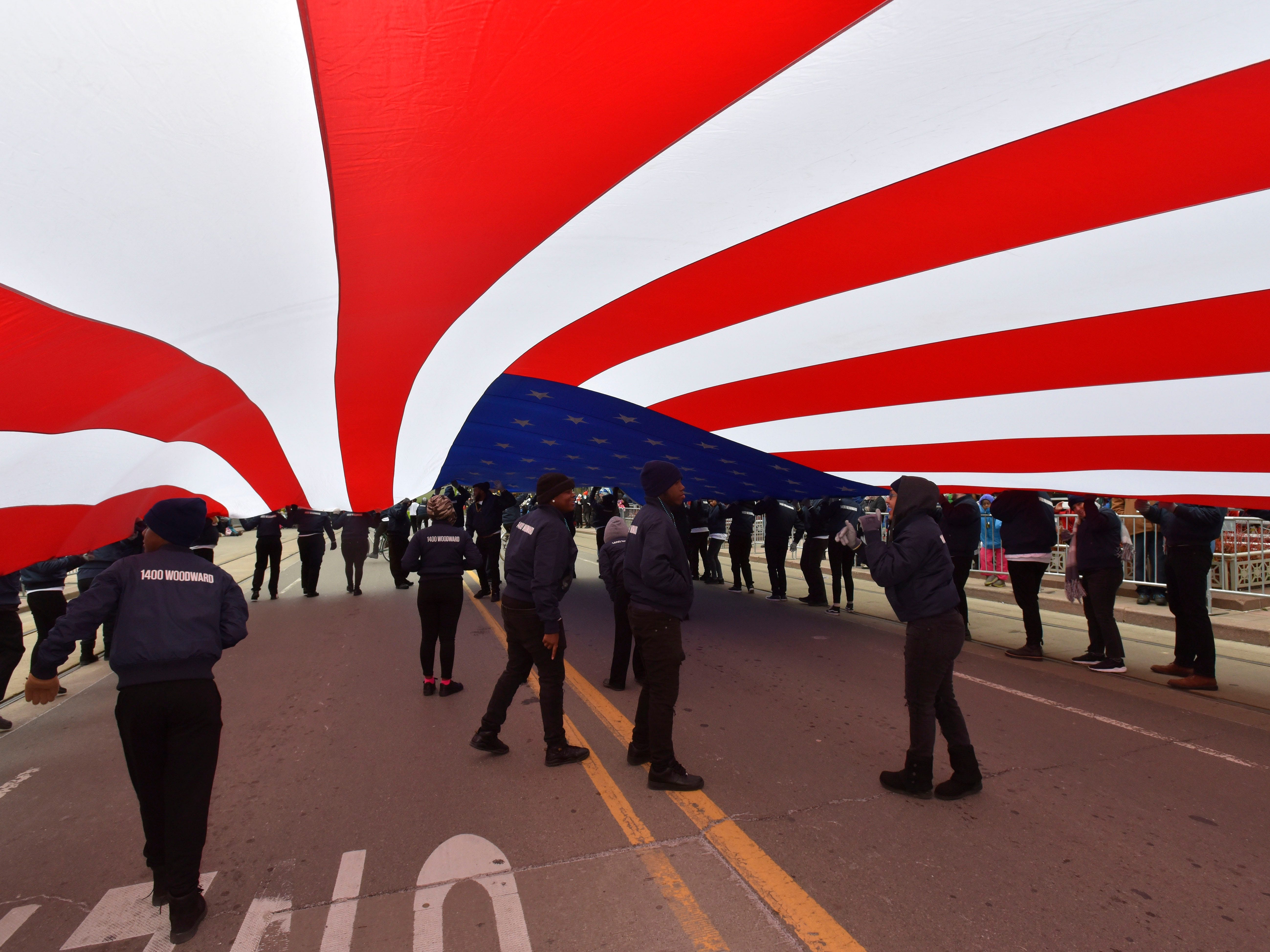 People walk under the U.S. flag from Shinola Detroit.