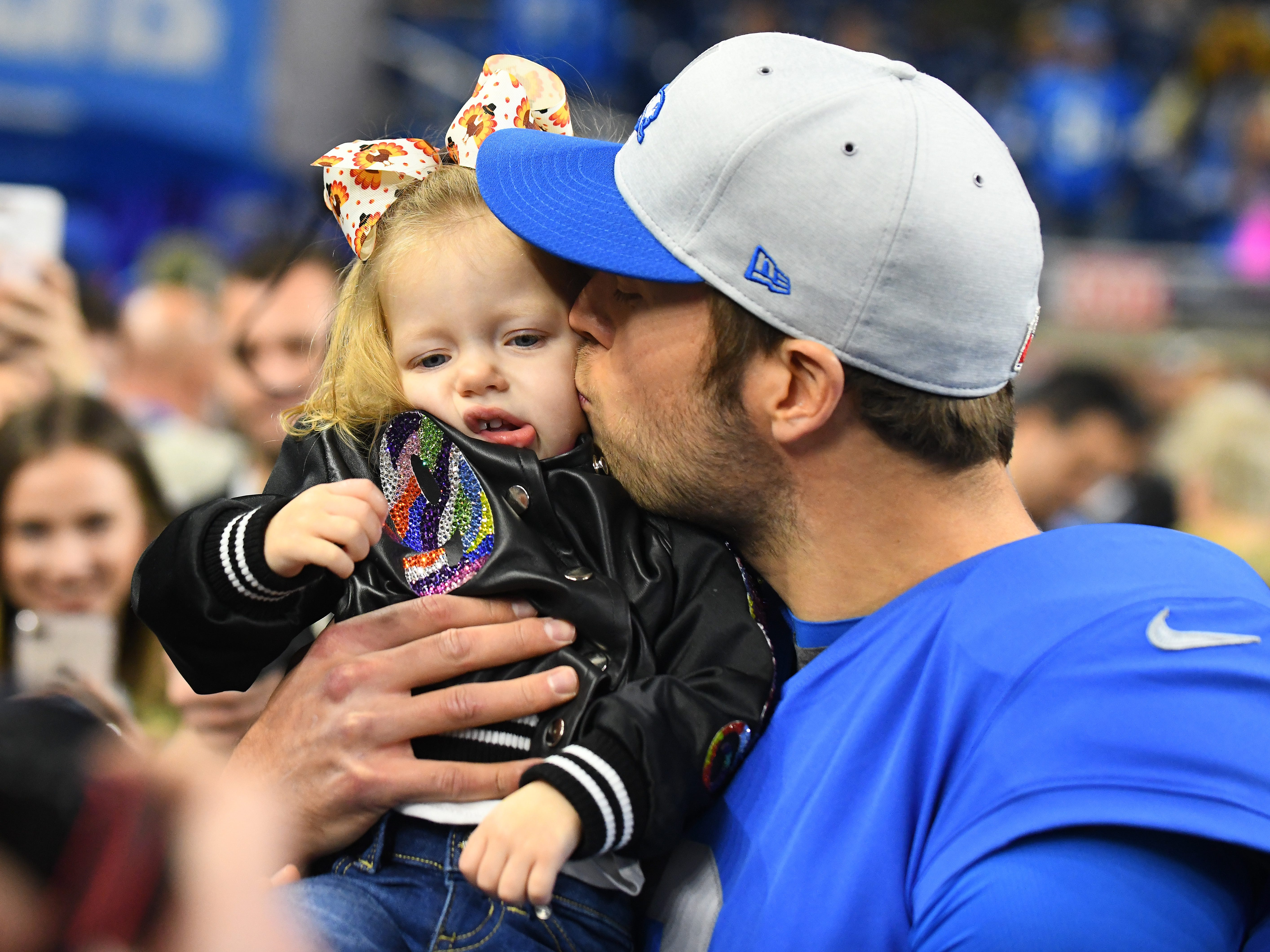 Lions quarterback Matthew Stafford gives one of his three daughters a kiss before heading out for warmups.