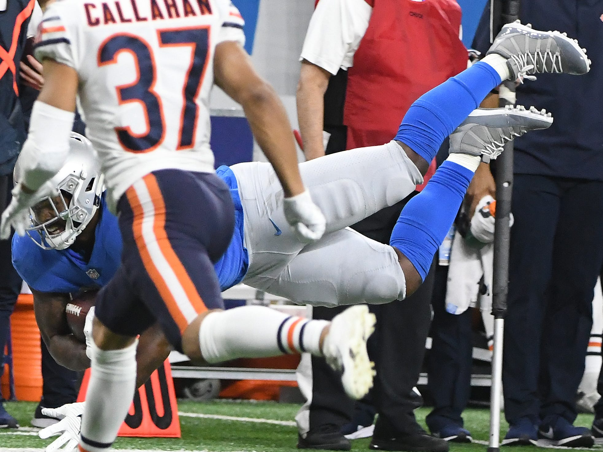 Lions' Michael Roberts dives for extra yardage along the sidelines with Bears' Bryce Callahan defending in the first quarter.