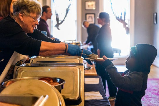 Earleen Boylls serves green beans to four-year-old Chris (last name withheld) during a free Thanksgiving buffet at Sauced in Evansville's Haynie's Corner Arts District, Thursday afternoon, Nov. 22, 2018. Chefs from Sauced, Bokeh Lounge and Dapper Pig teamed up to offer food to anyone from 11 a.m. to 3 p.m. on the Thanksgiving holiday.