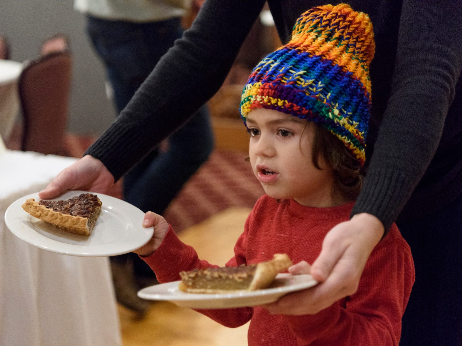 Silas Lyons, 5, helps his mother Dana Lyons deliver two slices of Pecan pie to their friends Judy and Bud Dugan, not pictured, during the free Thanksgiving Buffet held at Sauced in Evansville's Haynie's Corner Arts District, Thursday afternoon, Nov. 22, 2018.