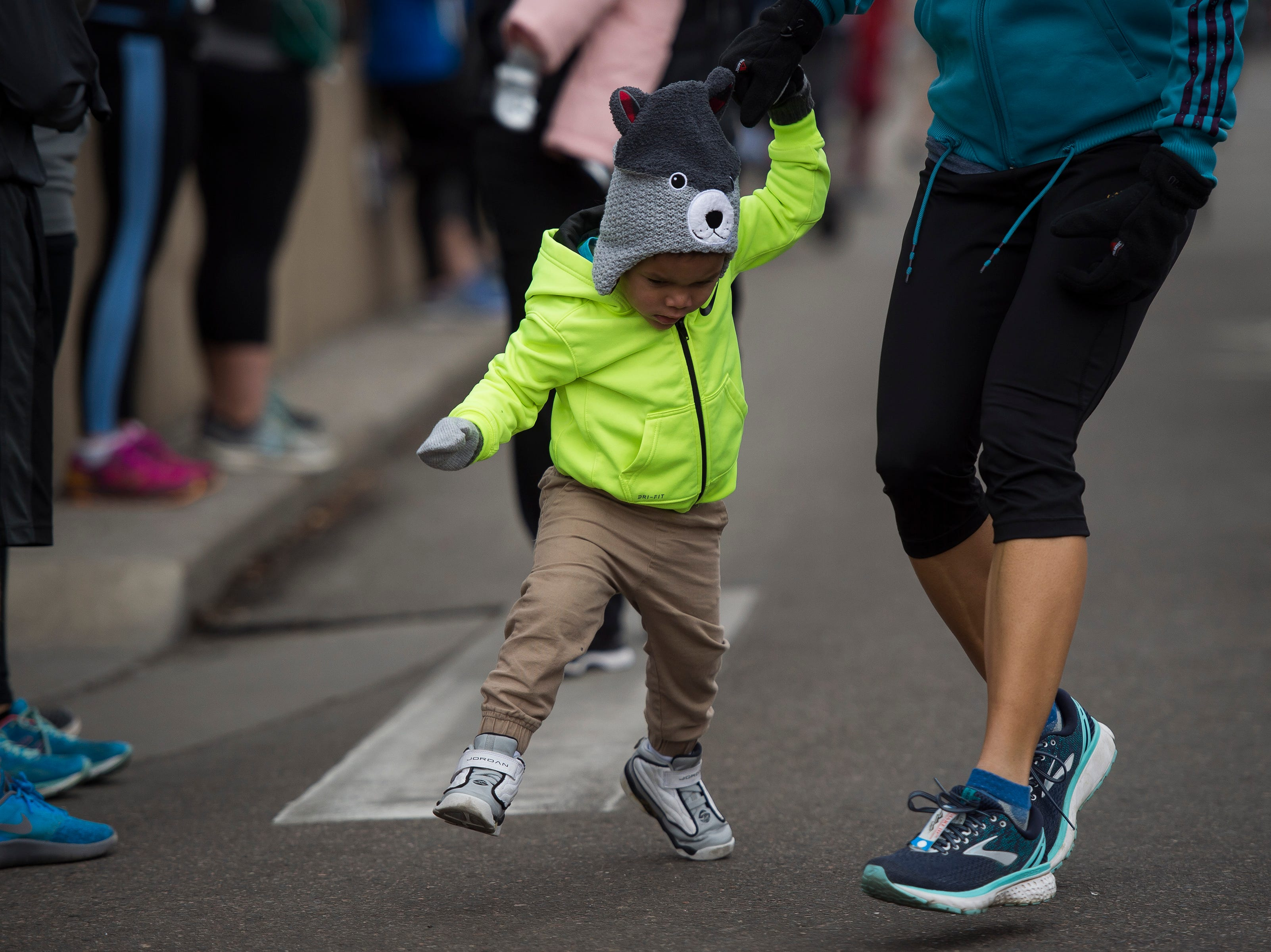 A young runner is helped along while participating in the kid's race during the Fort Collins Thanksgiving Day Run on Thursday, Nov. 22, 2018, in Old Town Fort Collins, Colo.
