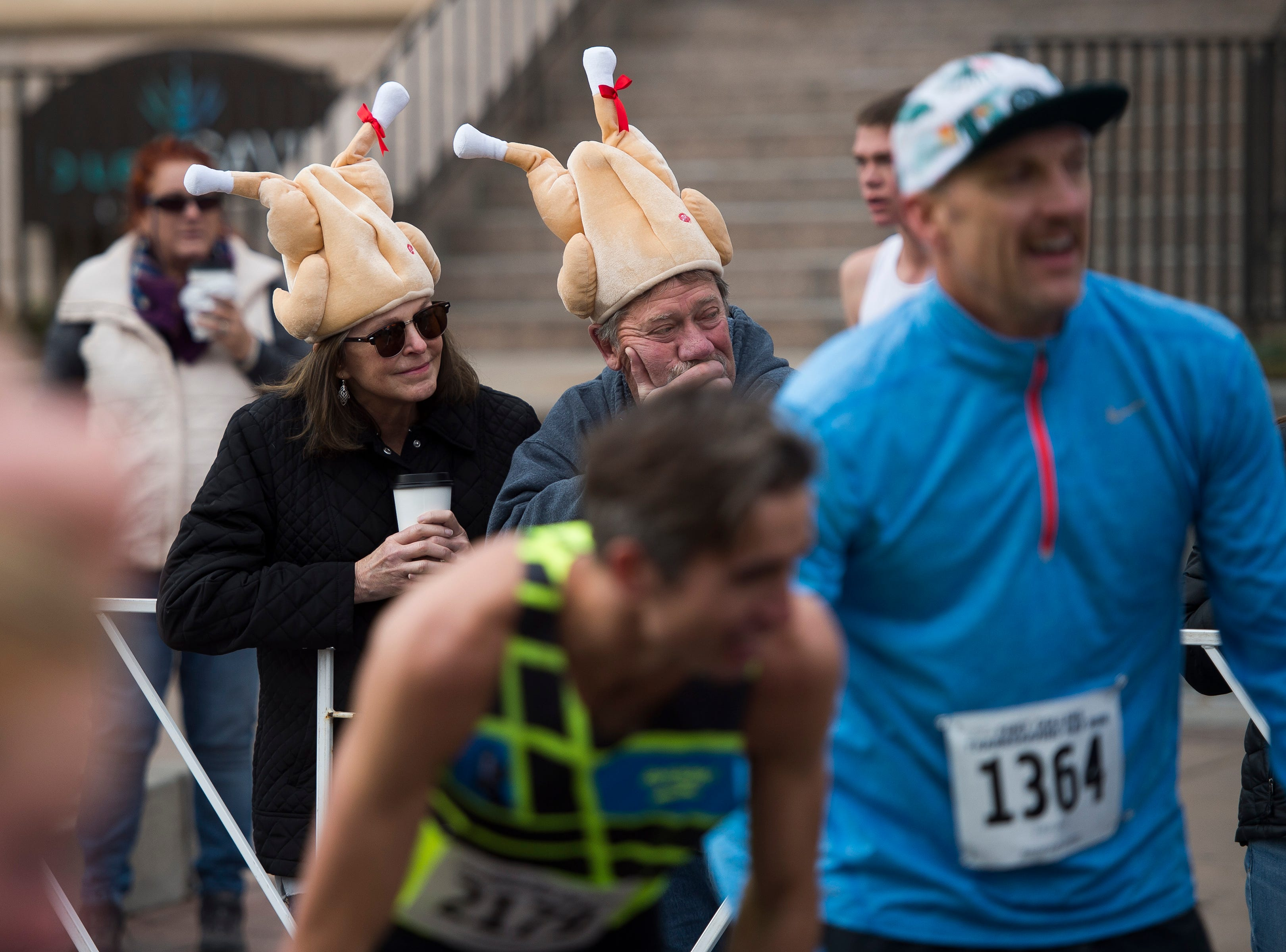 Fans wearing festive hats look on at the finish line during the Fort Collins Thanksgiving Day Run on Thursday, Nov. 22, 2018, in Old Town Fort Collins, Colo.