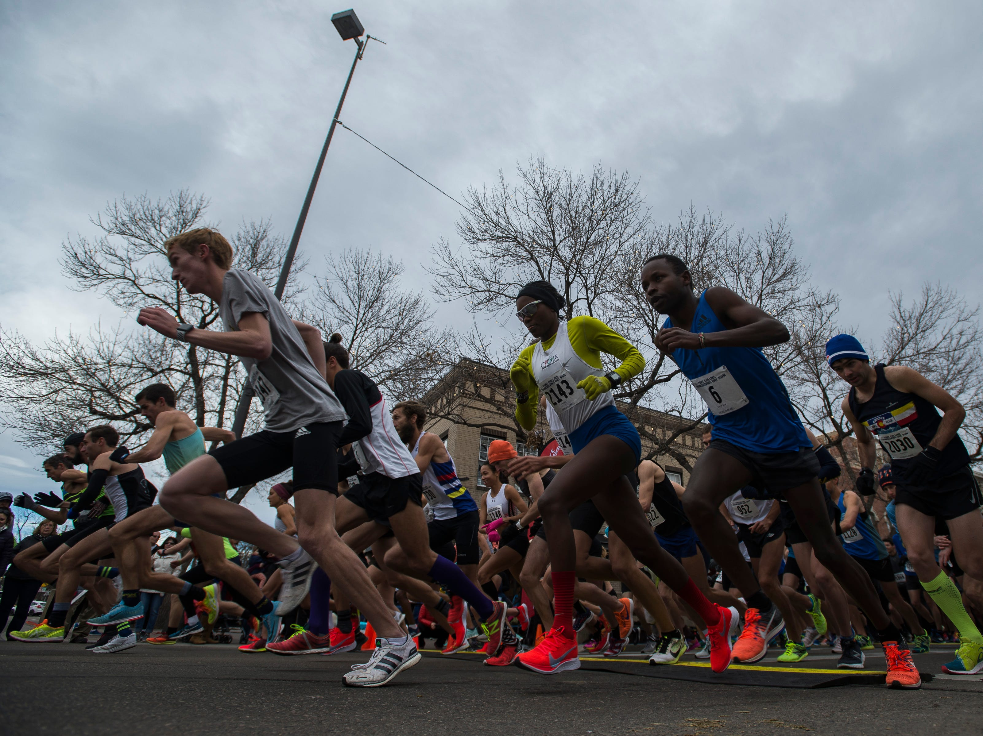Runners take off from the start line during the Fort Collins Thanksgiving Day Run on Thursday, Nov. 22, 2018, in Old Town Fort Collins, Colo.