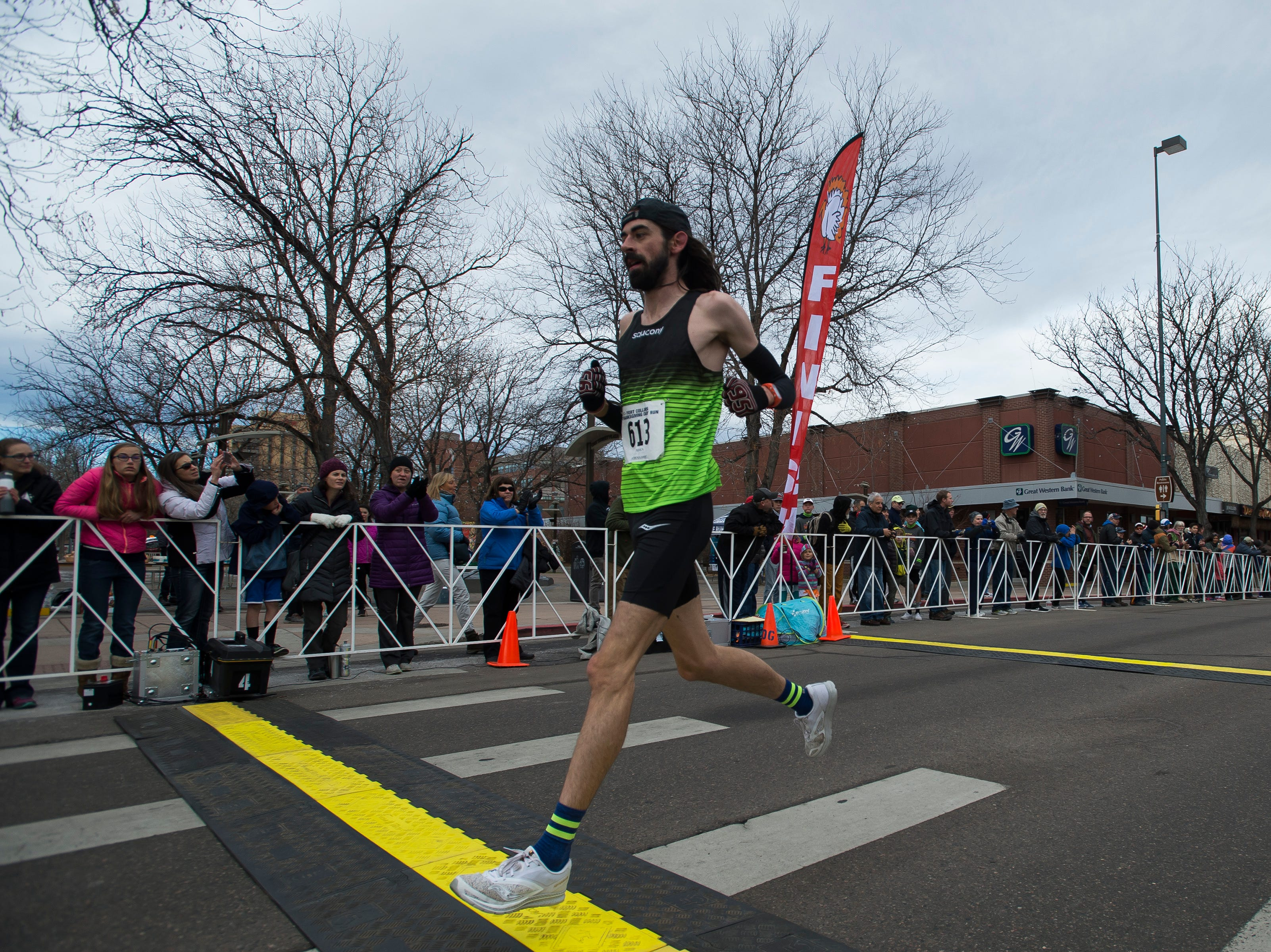 Noah Droddy crosses the finish line to become the first male finisher during the Fort Collins Thanksgiving Day Run on Thursday, Nov. 22, 2018, in Old Town Fort Collins, Colo.