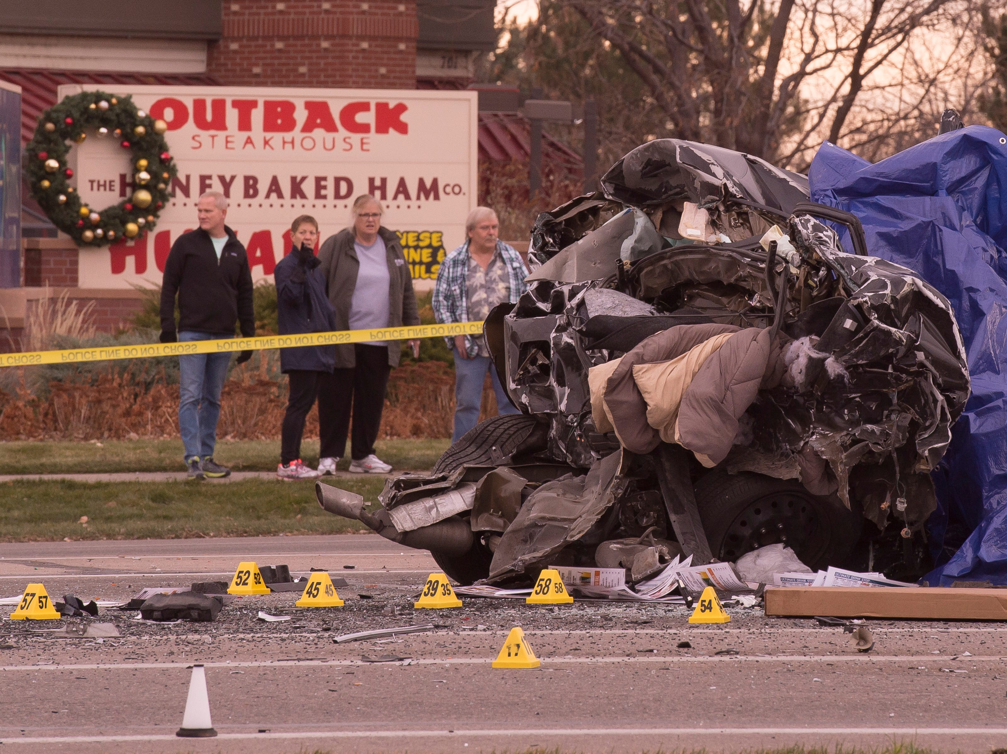 People look onto the scene of a crash with multiple fatalities and involving at least four vehicles on Thursday, Nov. 22, 2018, at the intersection of East Harmony Road and East Boardwalk Drive in Fort Collins, Colo.