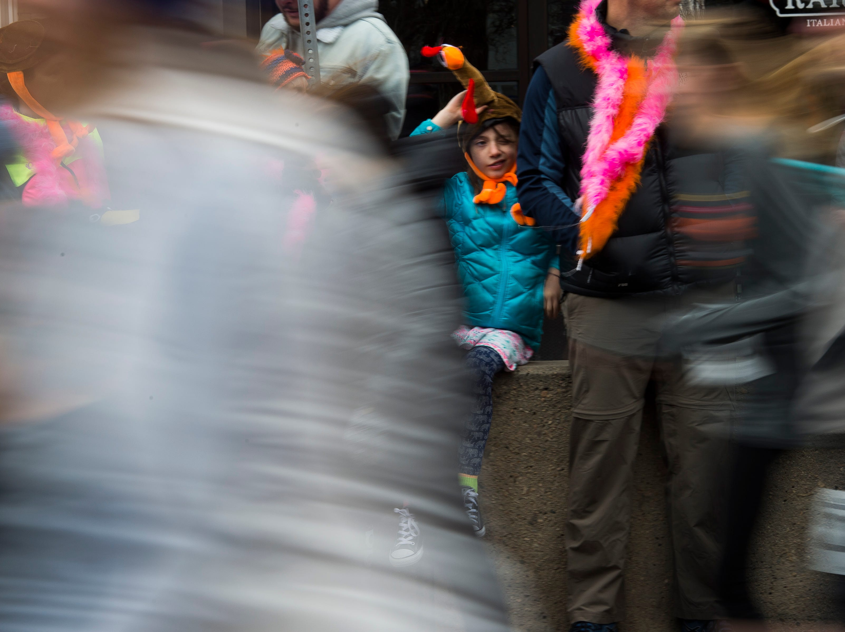 A young fan looks on just after the start line during the Fort Collins Thanksgiving Day Run on Thursday, Nov. 22, 2018, in Old Town Fort Collins, Colo.