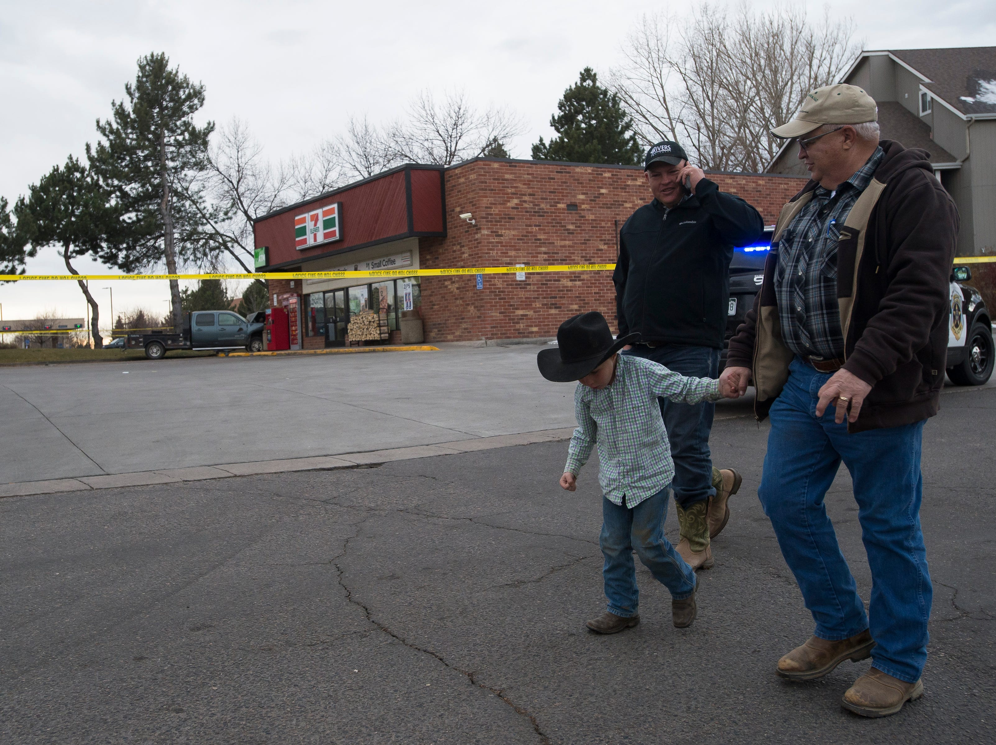 Dallas Schleining, left, talks on the phone while walking with his son Duke, 5, and his father Jim, past Dallas' truck that was stolen and involved in a crash with multiple fatalities, and then crashed into the corner of a gas station on Thursday, Nov. 22, 2018, at the intersection of East Harmony Road and East Boardwalk Drive in Fort Collins, Colo.