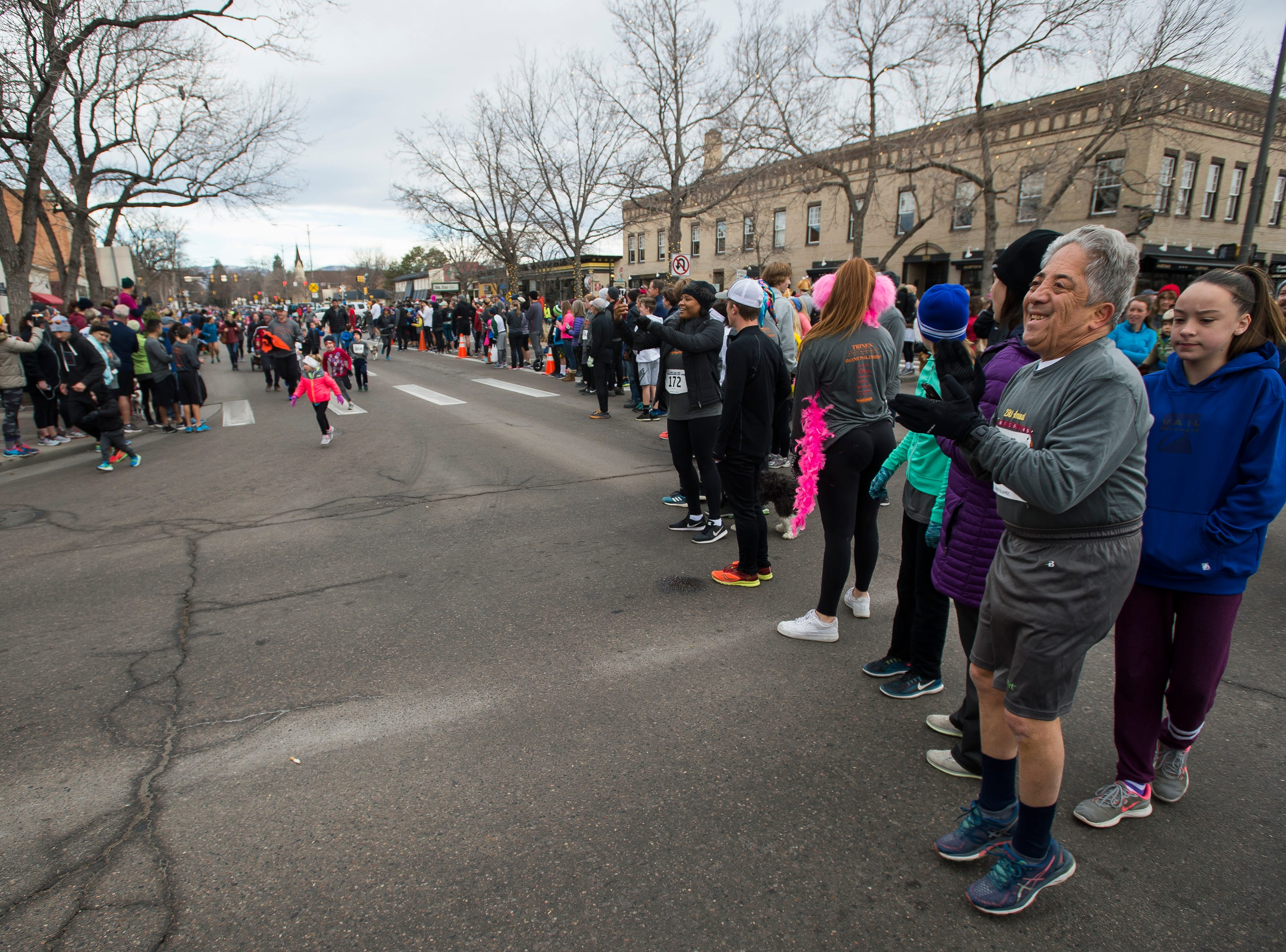 State Sen. John Kefalas, right, cheers on young runners participating in the kid's run during the Fort Collins Thanksgiving Day Run on Thursday, Nov. 22, 2018, in Old Town Fort Collins, Colo.