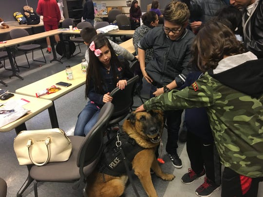 Latinx community members meet a Fort Collins Police Services K-9 at a tour of the police department.