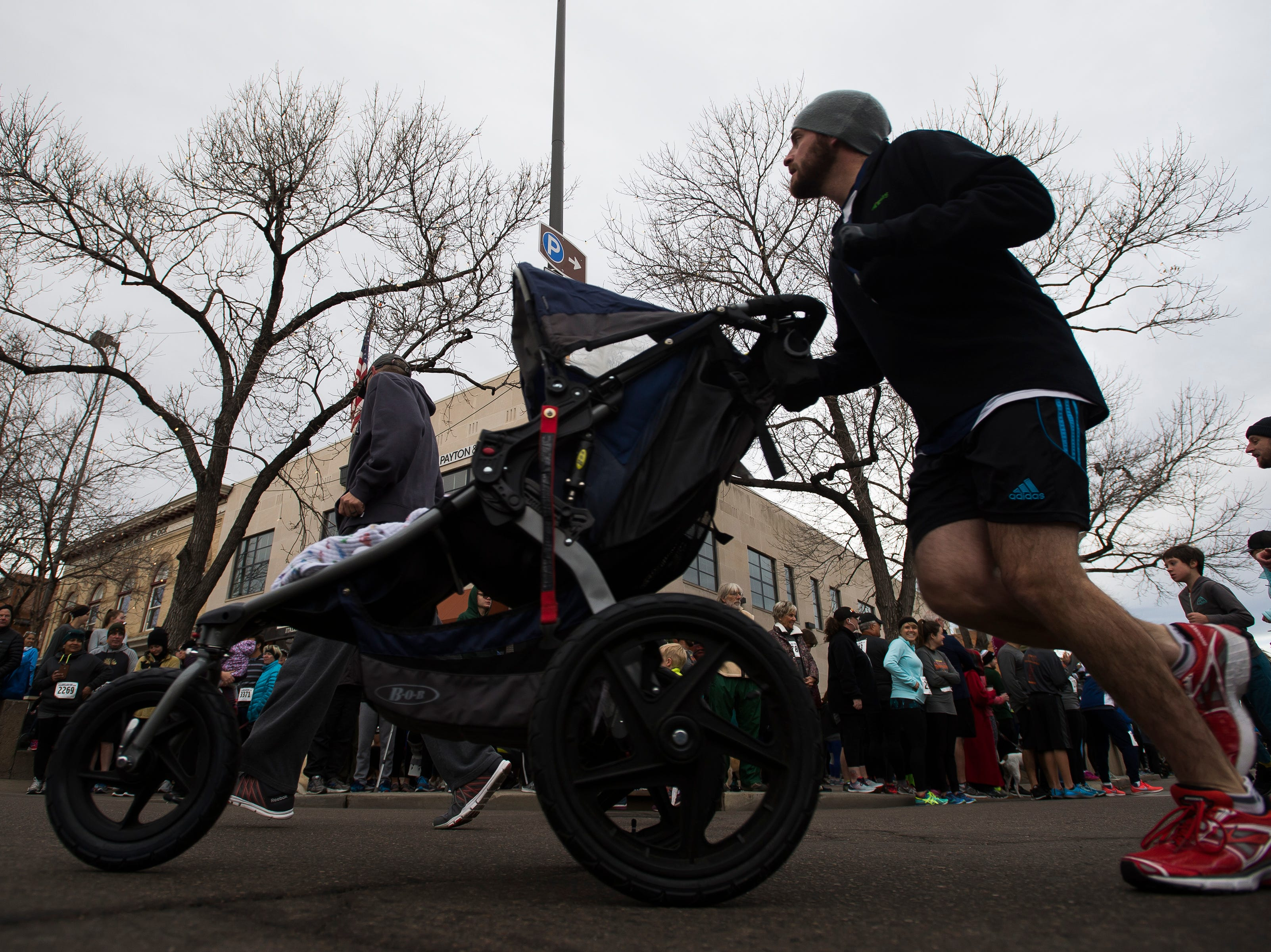 A runner pushes a stroller during the Fort Collins Thanksgiving Day Run on Thursday, Nov. 22, 2018, in Old Town Fort Collins, Colo.