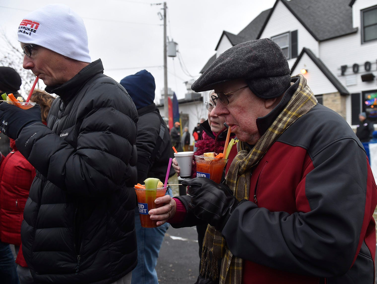 Dan Carlson of Fox Point, left, and his father-in-law Dick Farrell of Baileys Harbor trying out the local parade beverages at the Thanksgiving Day Parade in Jacksonport on Thursday, Nov. 22, 2018. Tina M. Gohr/USA TODAY NETWORK-Wisconsin