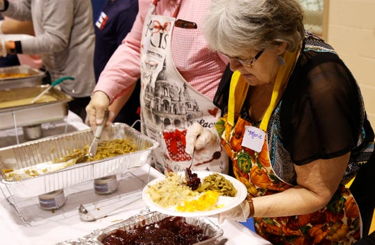 Marie Bowers serves up cranberry sauce during the Thanksgiving meal hosted by Haven of Rest and held at First Presbyterian in Anderson Thursday, Nov. 22, 2018.