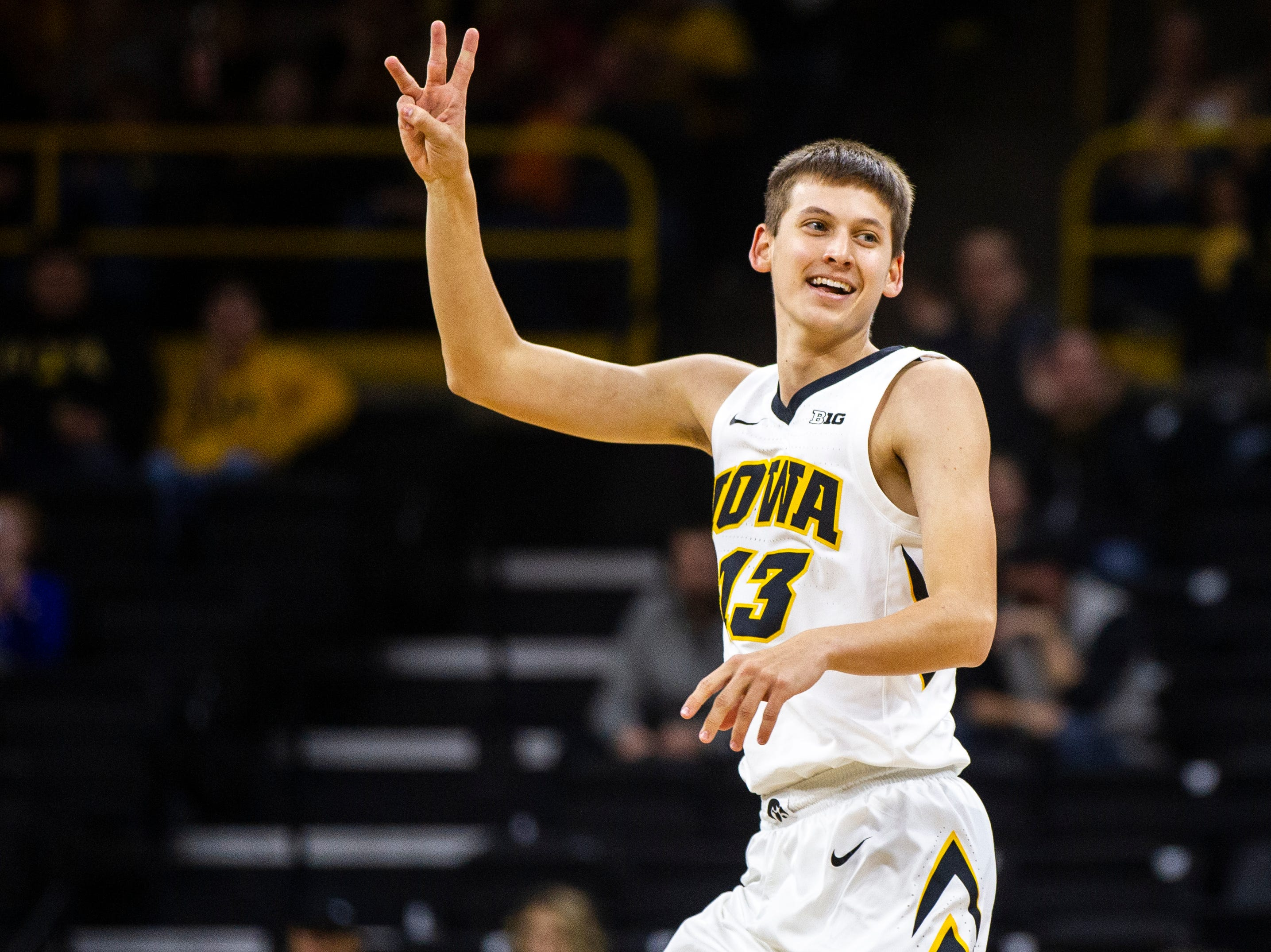 Iowa guard Austin Ash (13) holds up three fingers after making a 3-point basket during an NCAA men's basketball game on Wednesday, Nov. 21, 2018, at Carver-Hawkeye Arena in Iowa City.