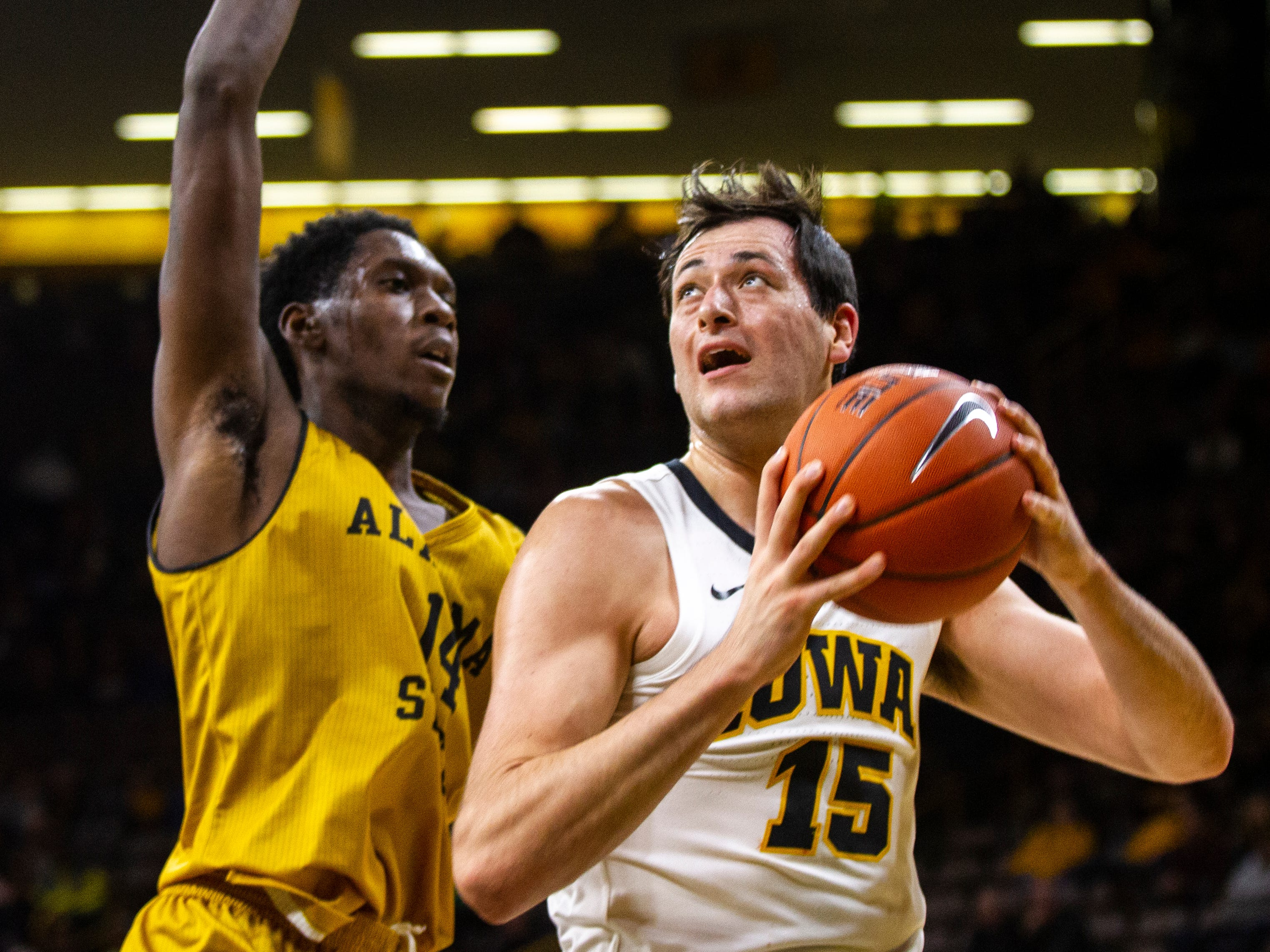 Iowa forward Ryan Kriener (15) attempts a shot while being defended by Alabama State's Ed Jones (14) during an NCAA men's basketball game on Wednesday, Nov. 21, 2018, at Carver-Hawkeye Arena in Iowa City.